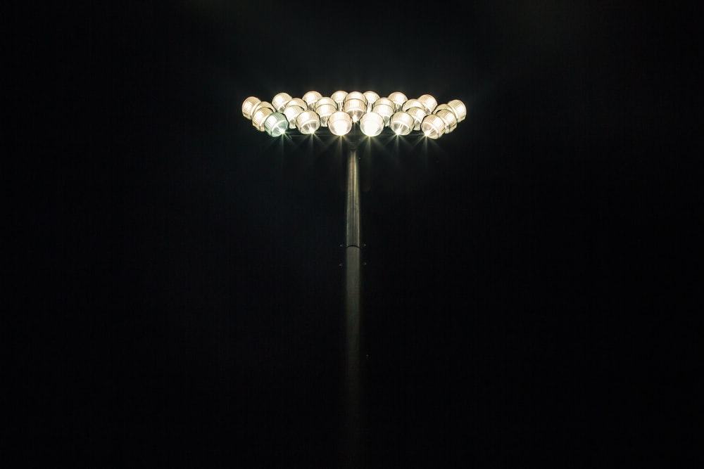 Floodlights shining at the top of a light pole with a pitch black background