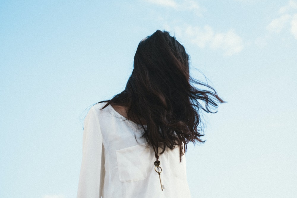 woman in white shirt under cloudy sky