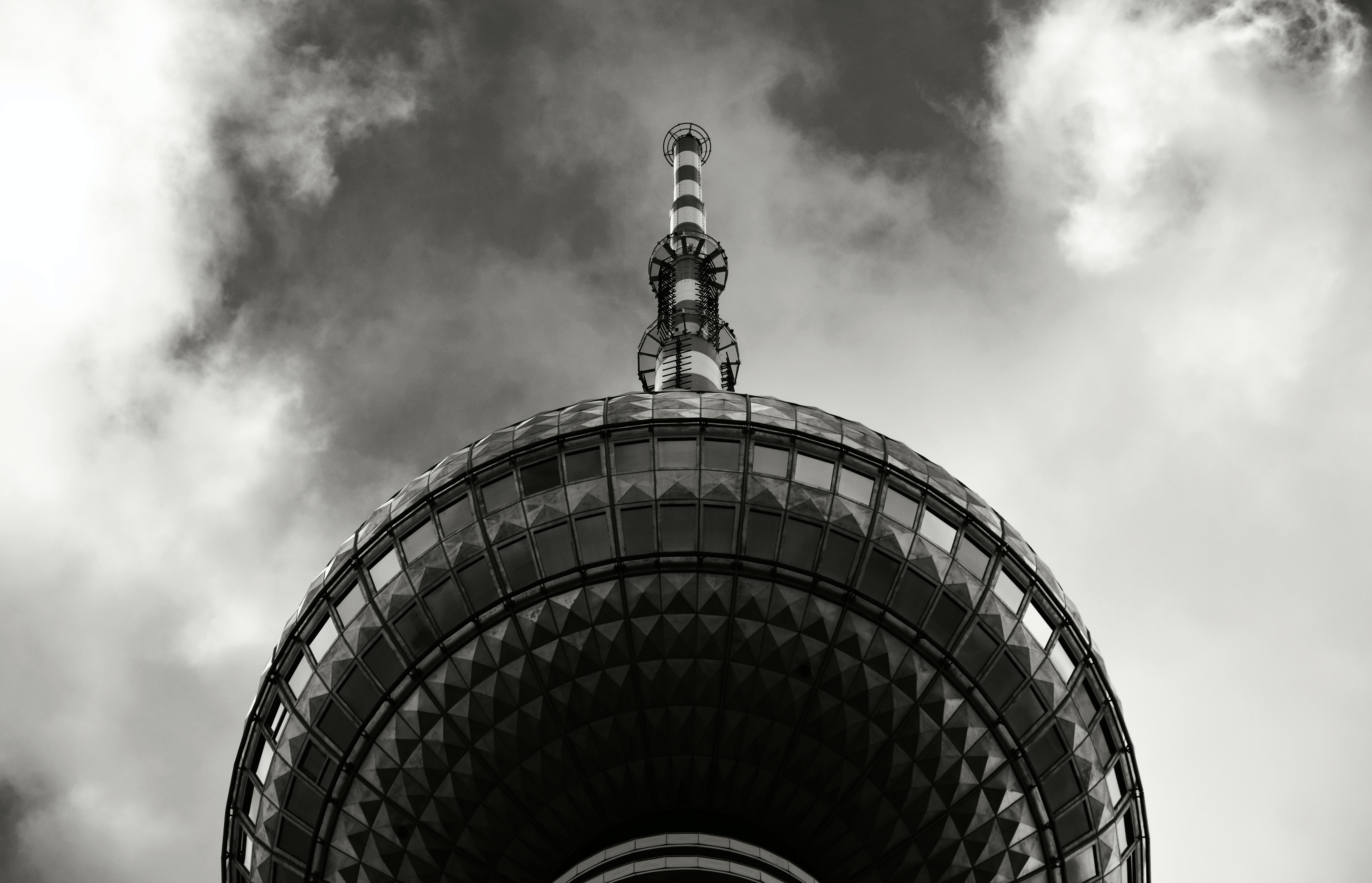 Black and white shot of modern tower from below with spire and clouds