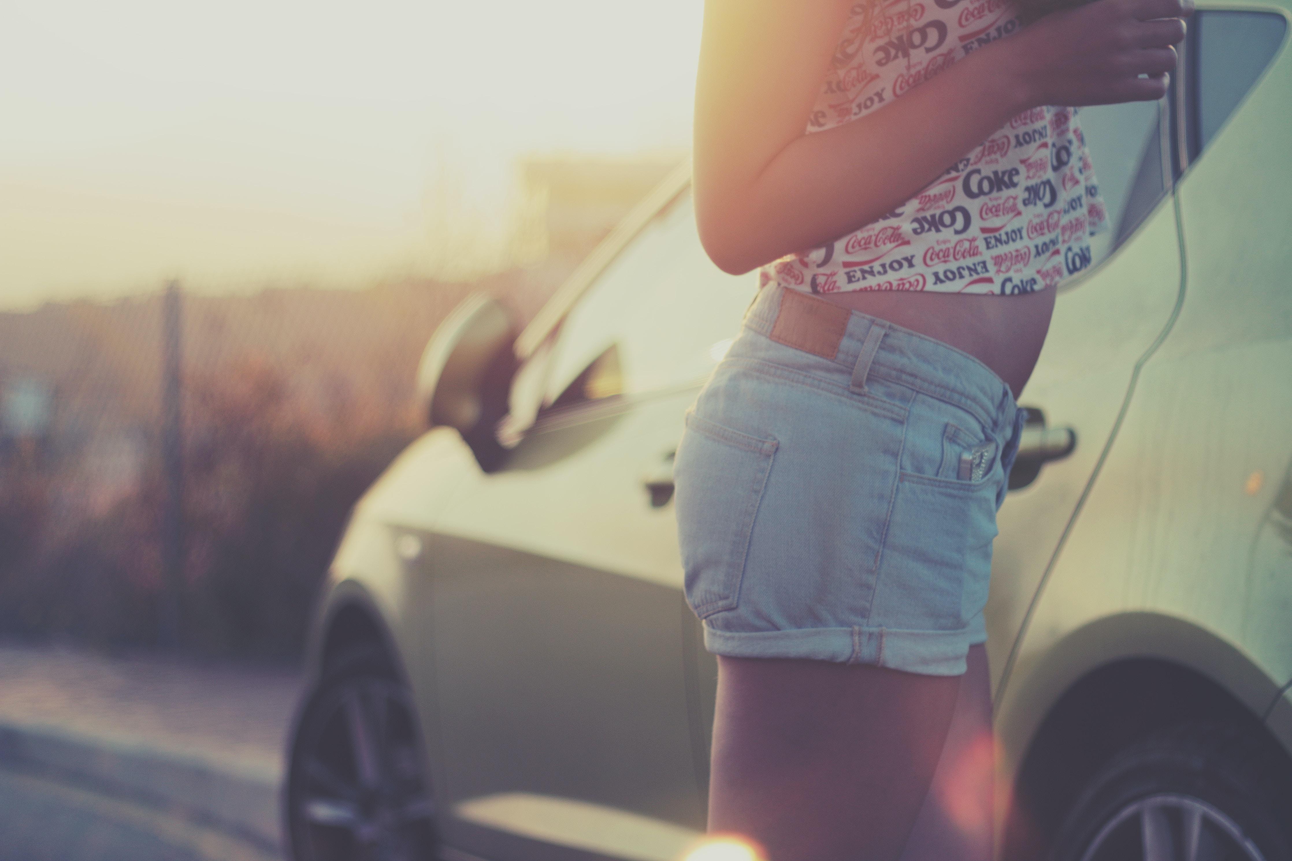 woman standing beside car