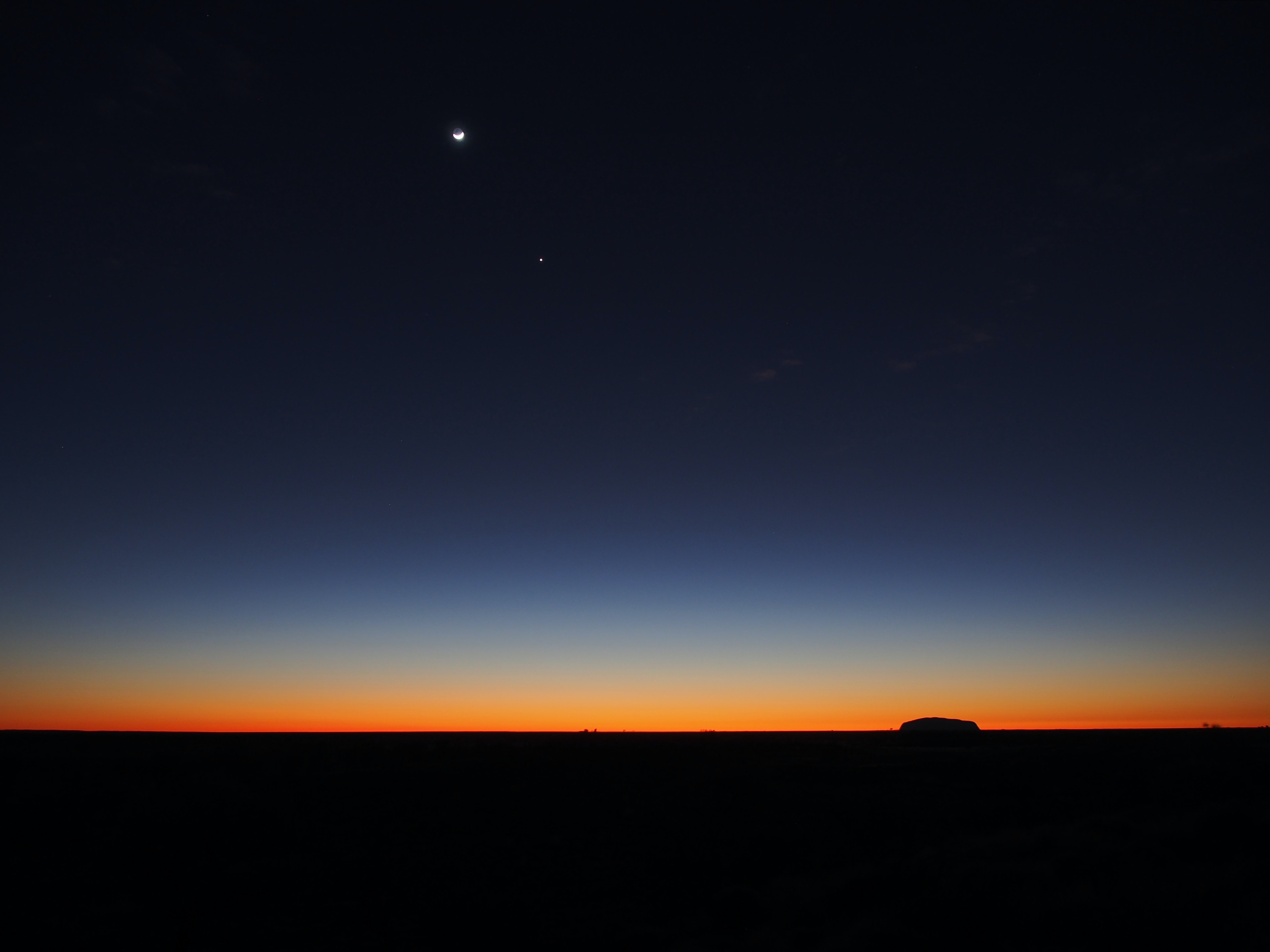 Uluru silhouetted against the moon with a lone star during twilight