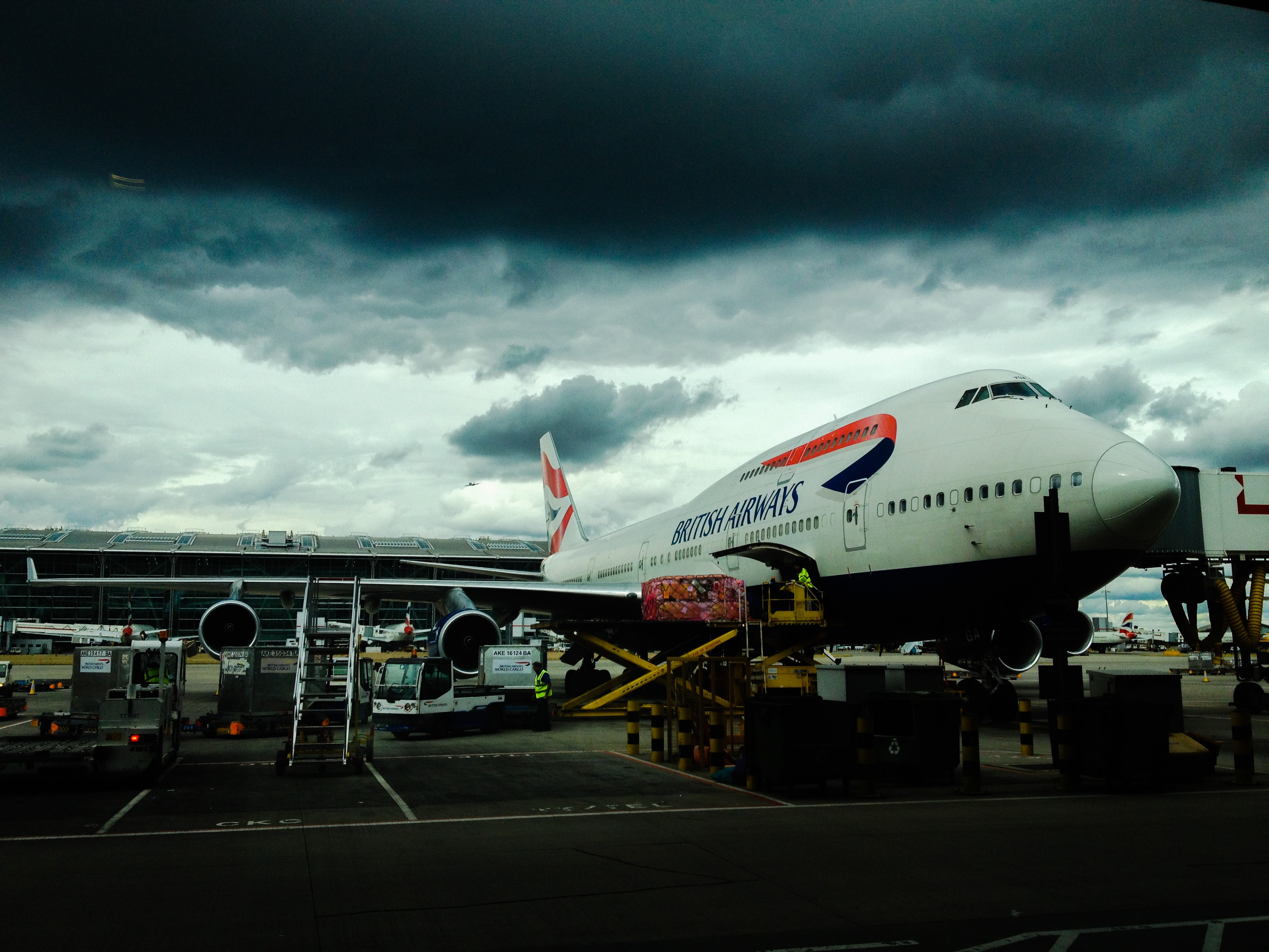 British Airways airplane on the ground of an airport under dark cloudy skies