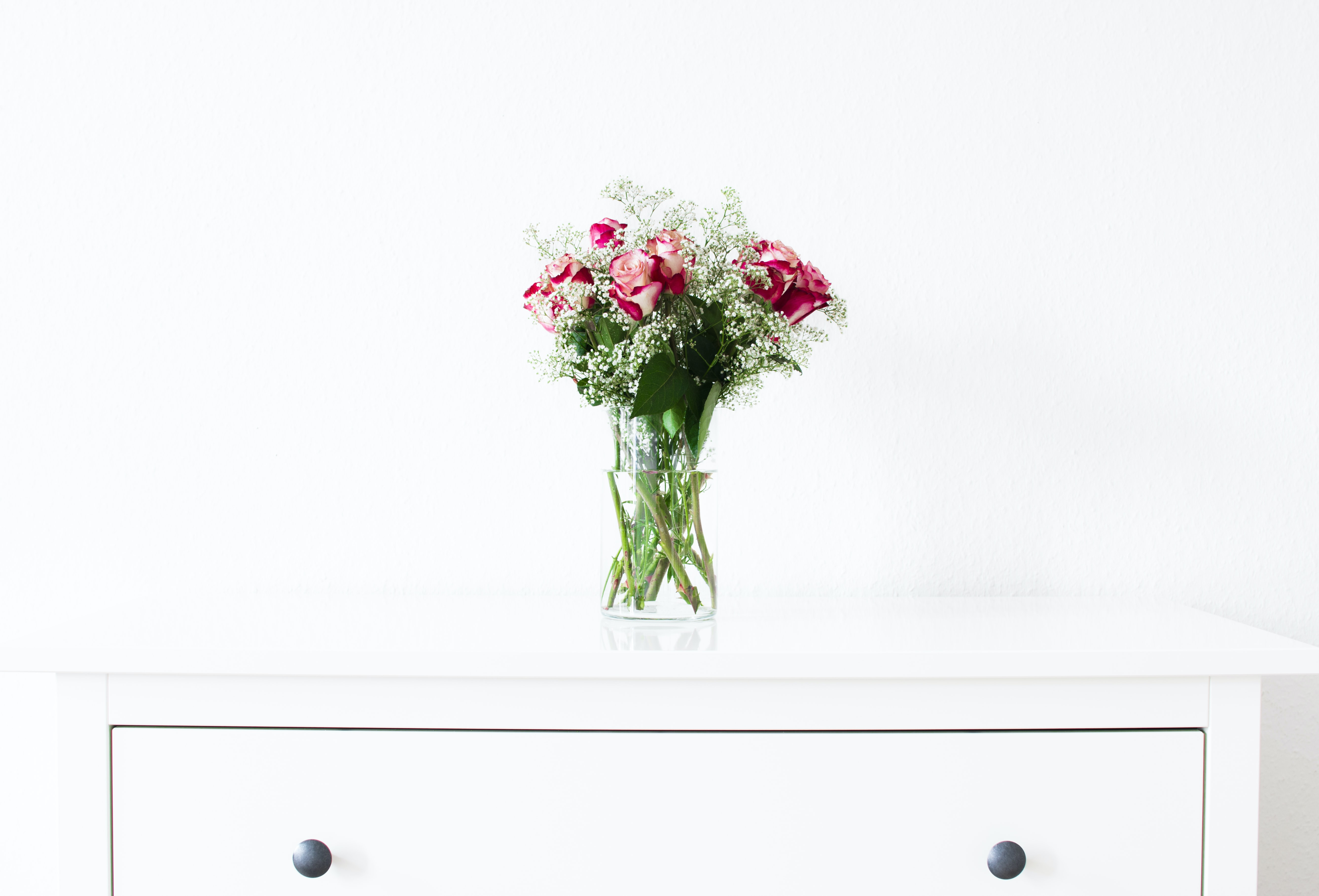 A bouquet of roses in a glass vase on a white cabinet