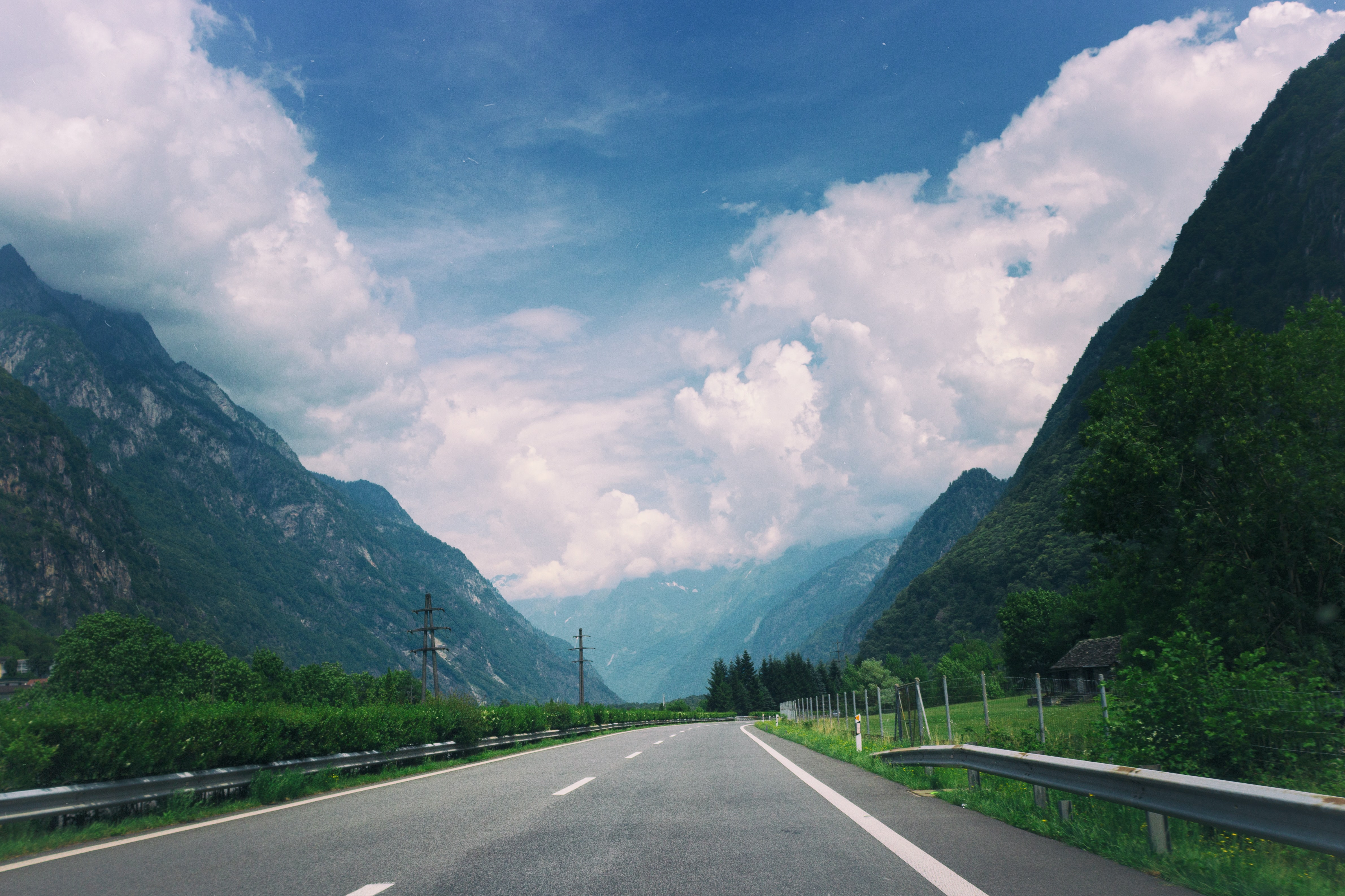 An empty road in a rural mountain valley on a cloudy day