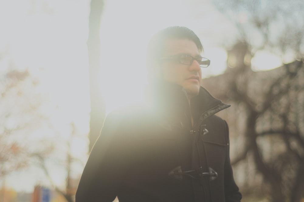 man wearing black jacket and eyeglasses