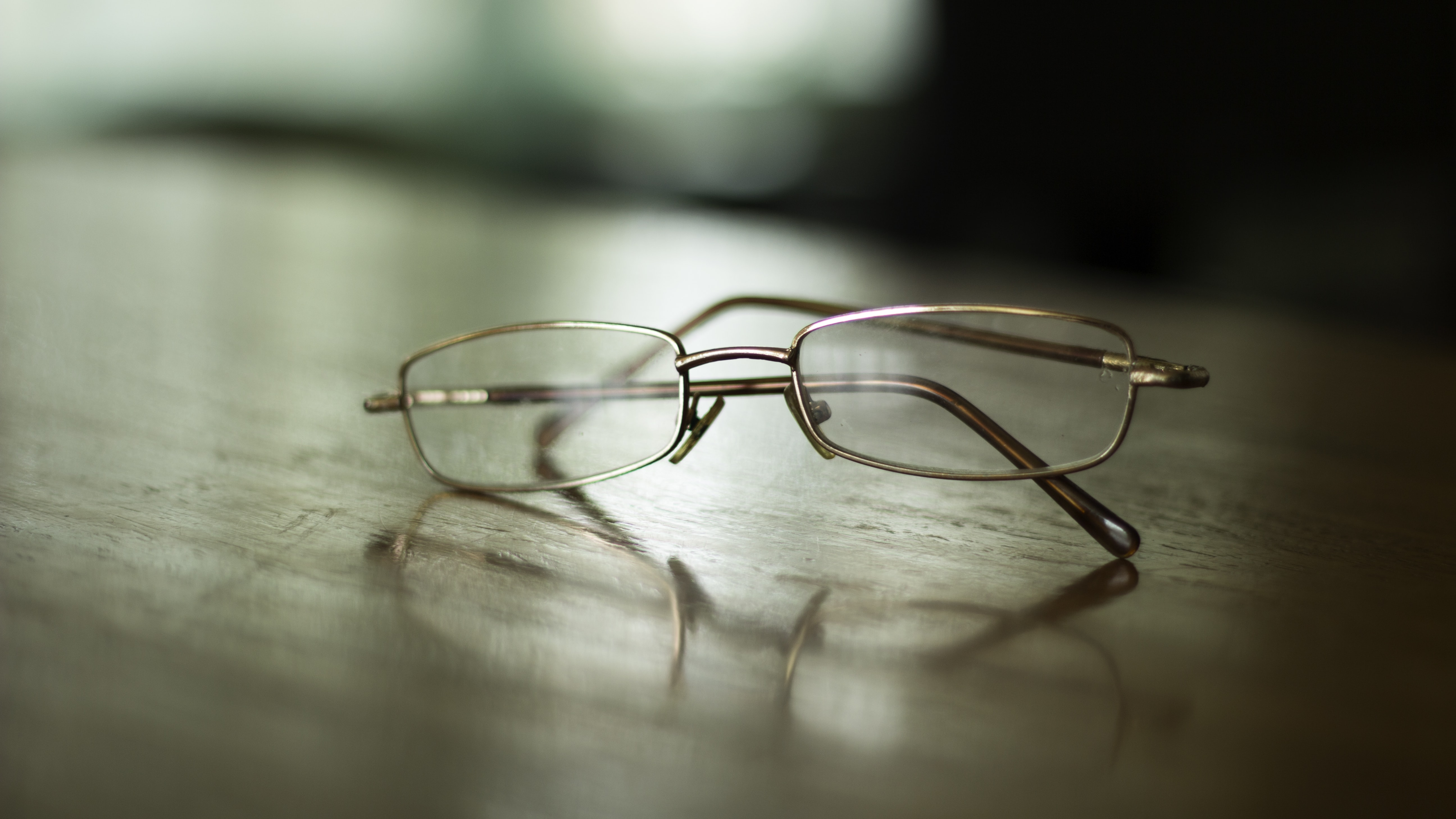 Close-up of a pair of glasses on a wooden surface