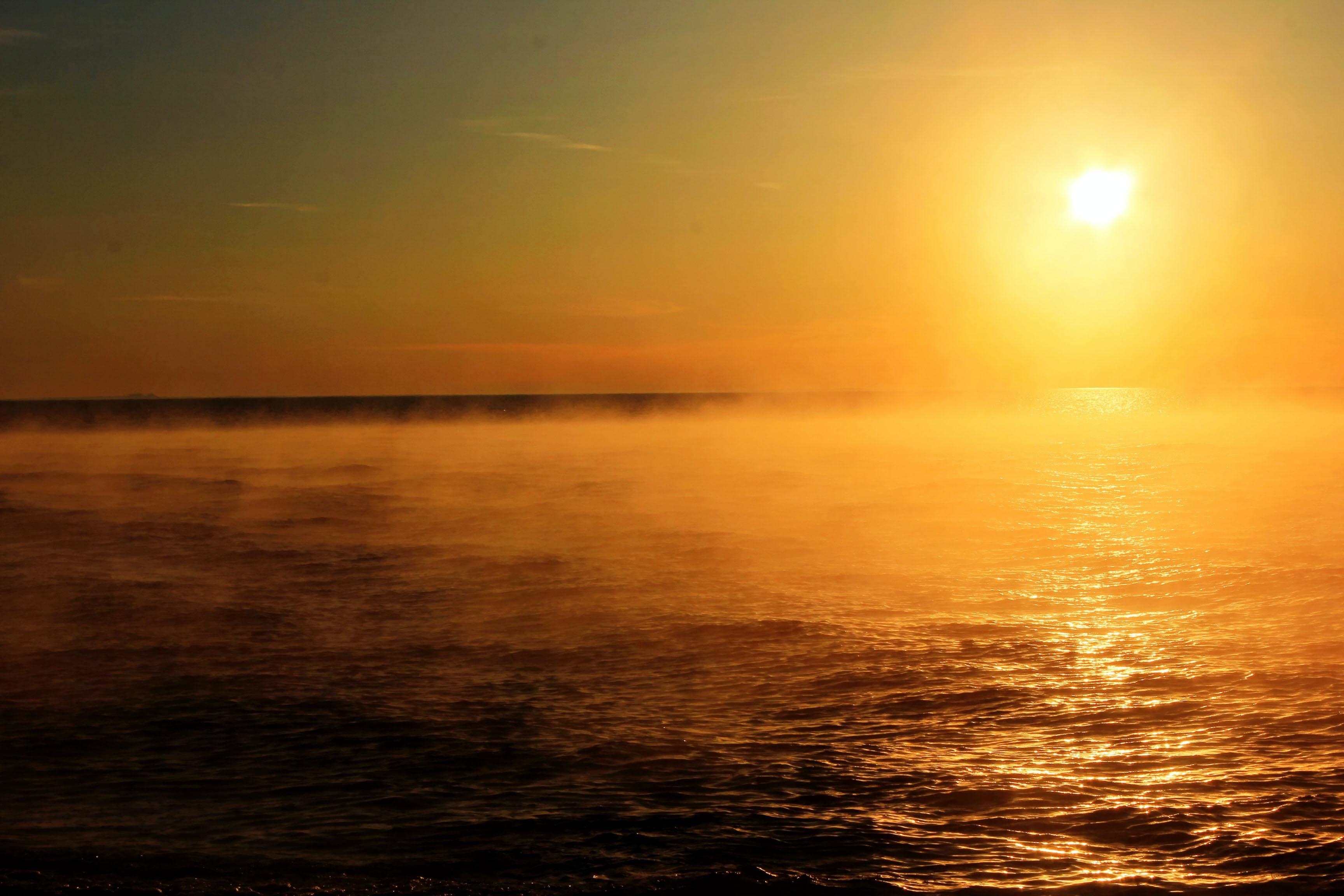 Sun setting over open waters, illuminating ocean