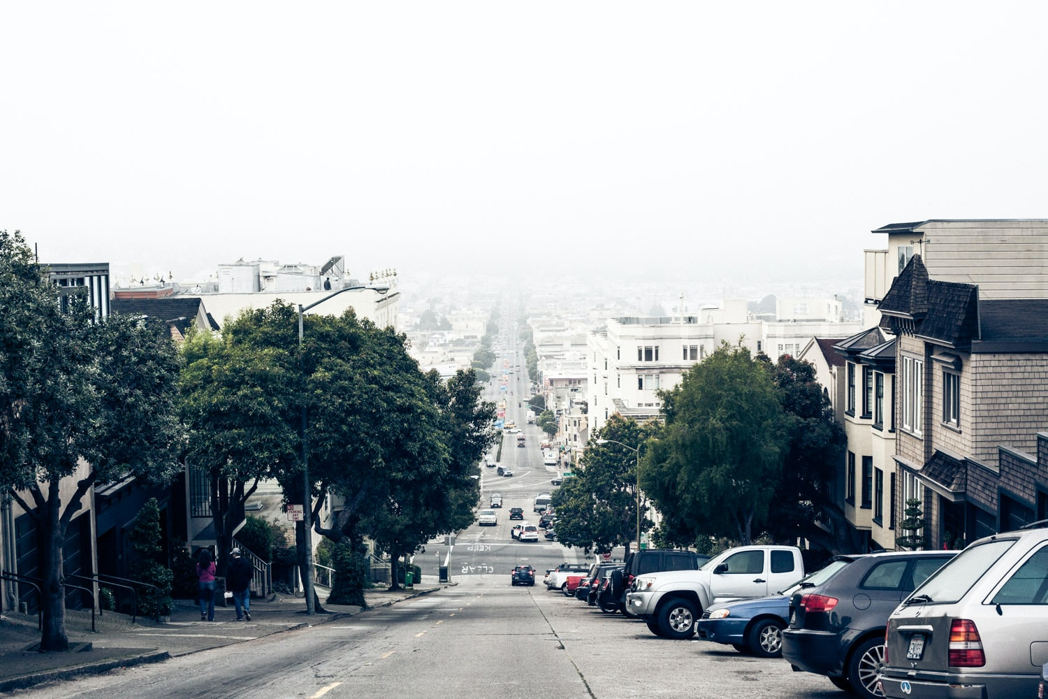 Street at the top of a hill lined with houses and cars with fog in the distance