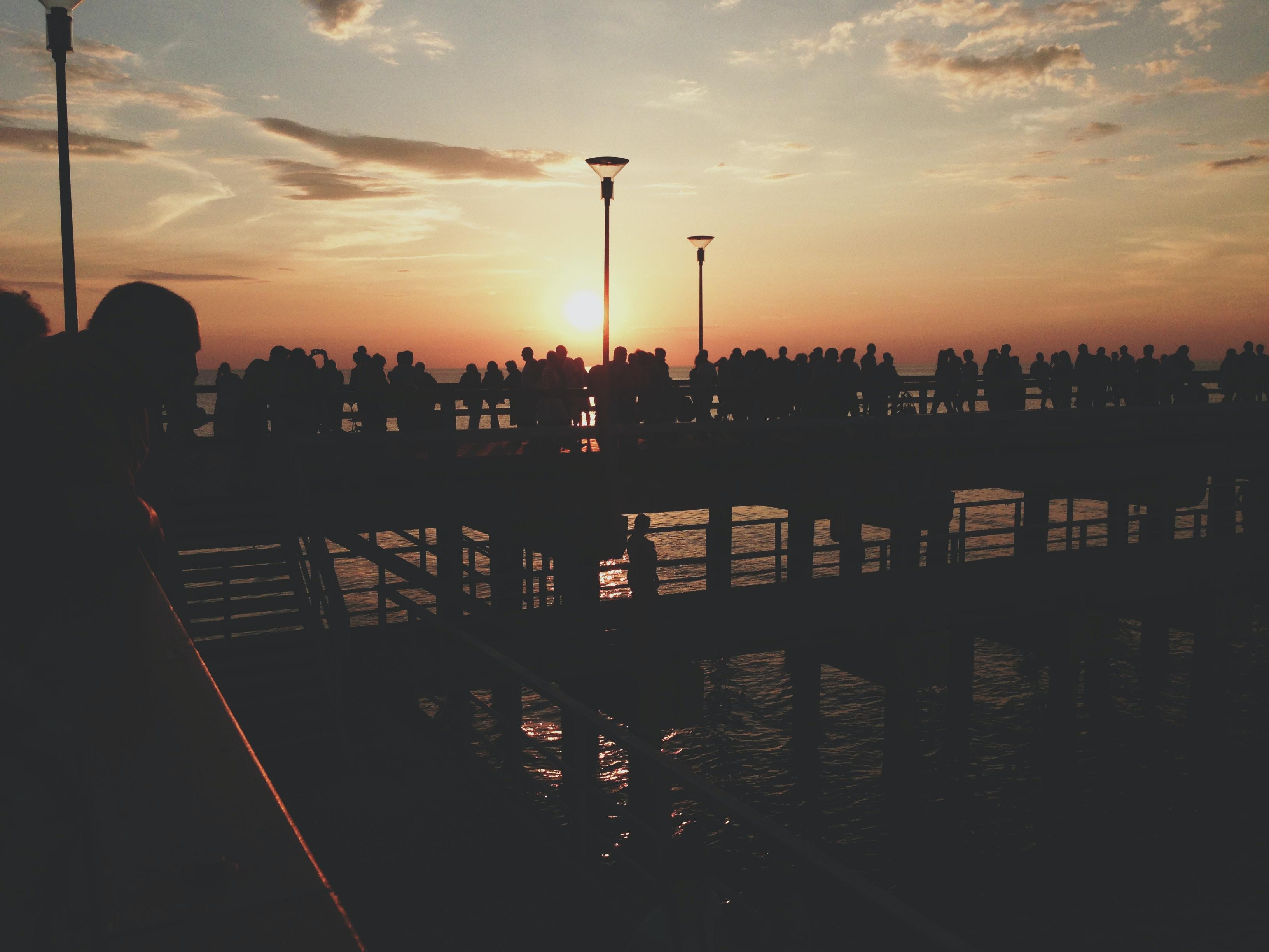 silhouette of people on bridge