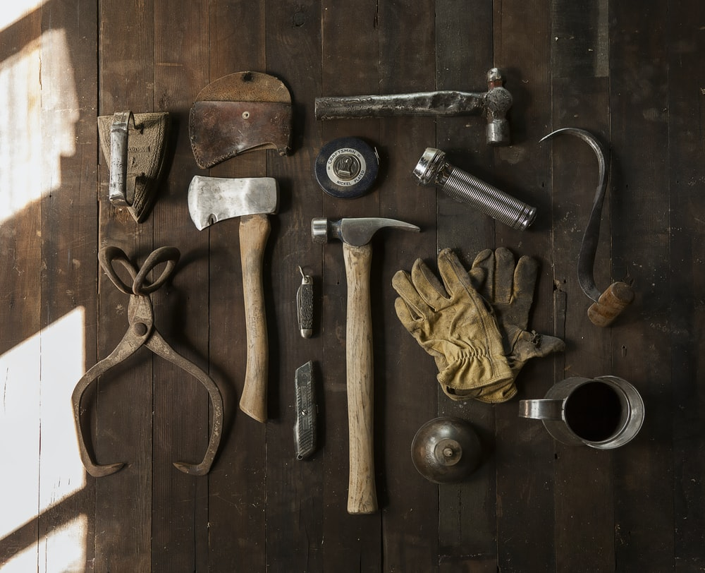 clothes iron, hammer, axe, flashlight and pitcher on brown wooden table
