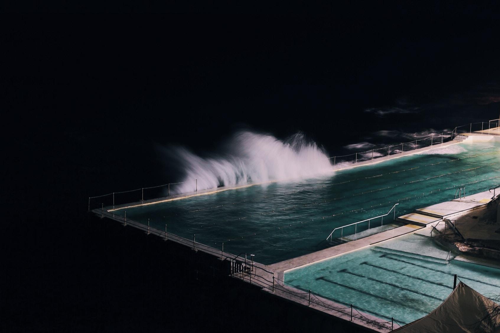 rectangular blue swimming pool during night time