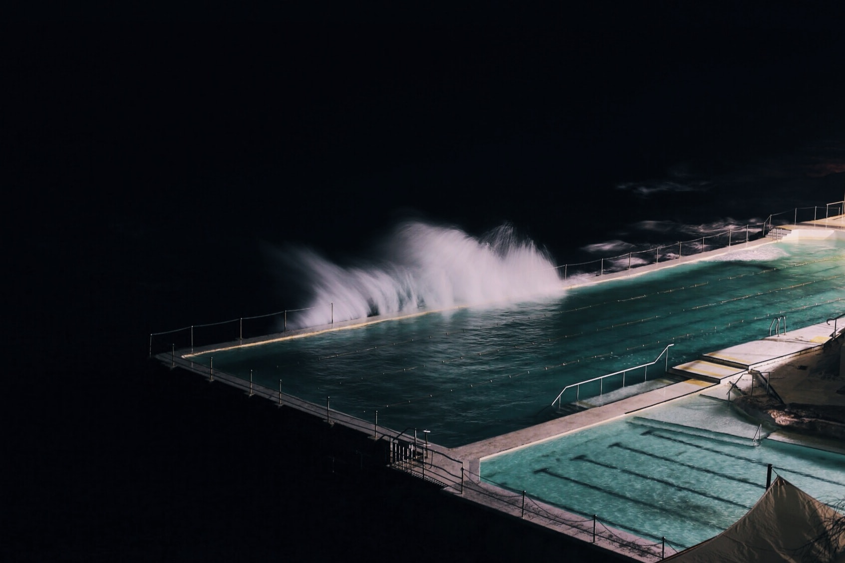 Bondi Beach at night with waves from the ocean splashing into it
