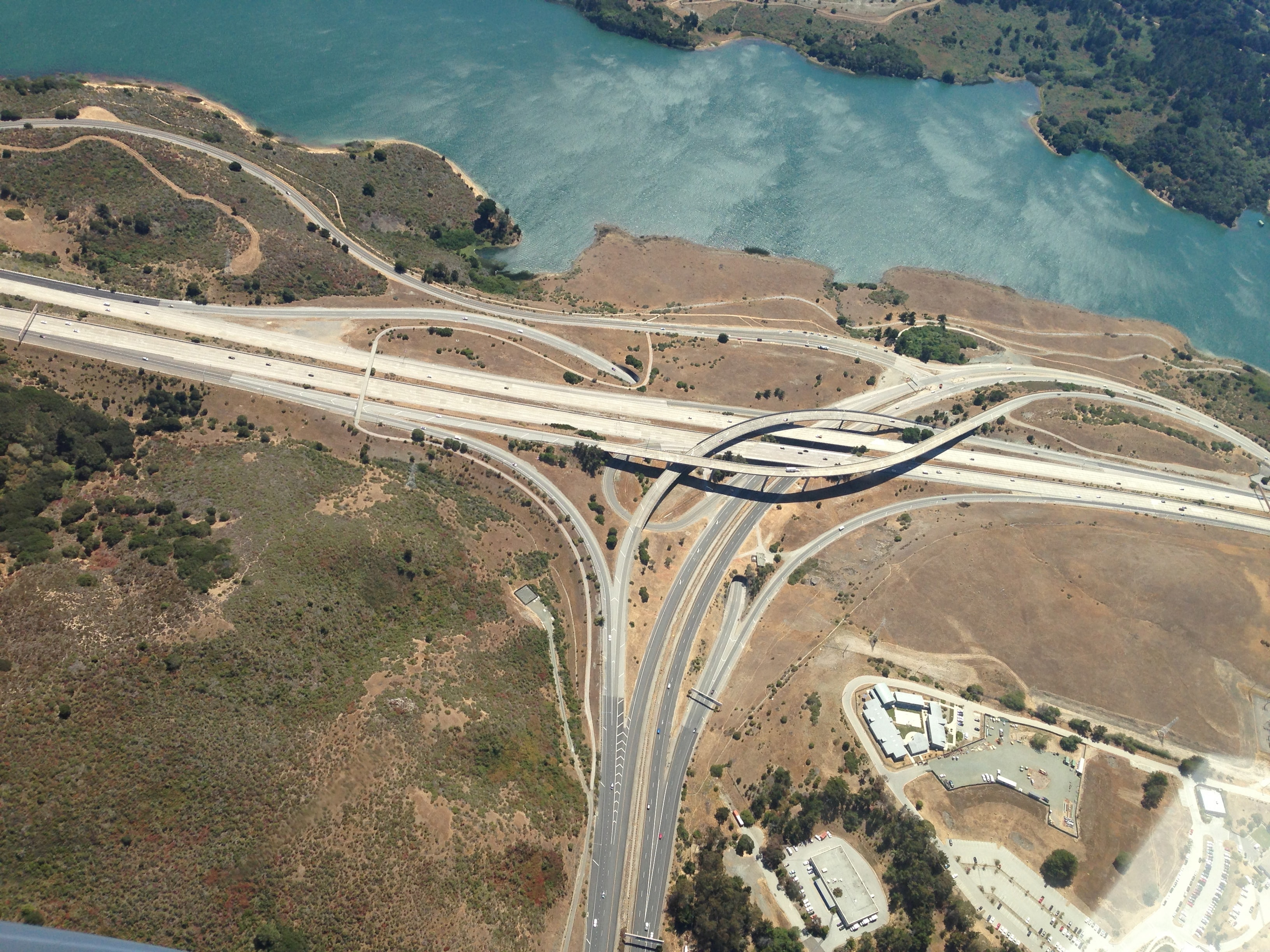 A drone shot of a road interchange near a river