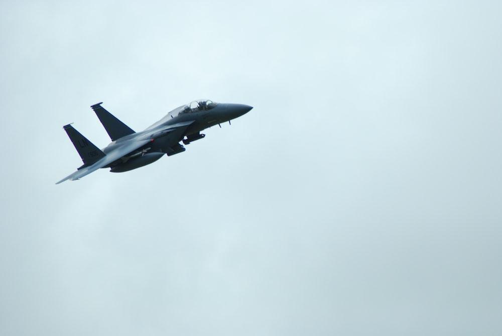 black flight plane on sky
