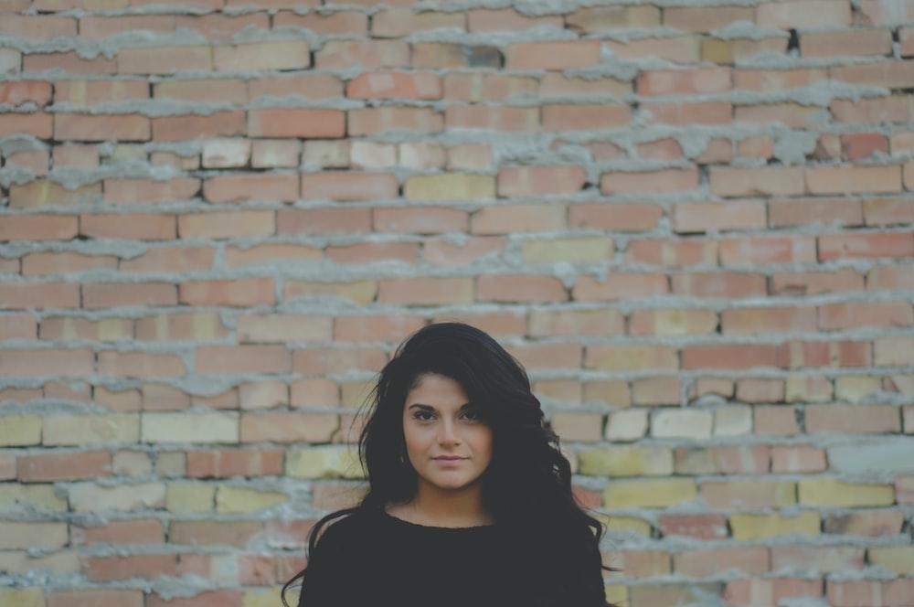 tilt shift lens photography of woman standing near brown brick wall