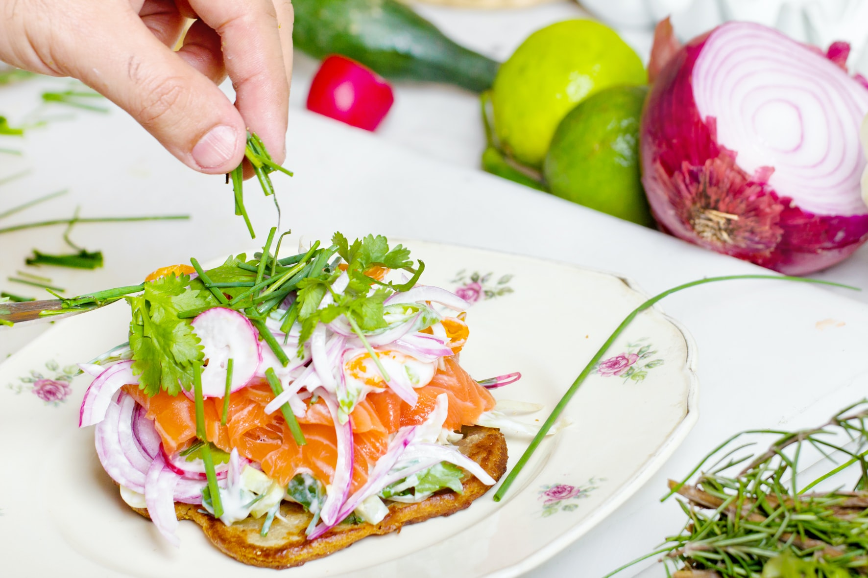 Hand sprinkling fresh dill on toast with salmon, onions, and vegetables