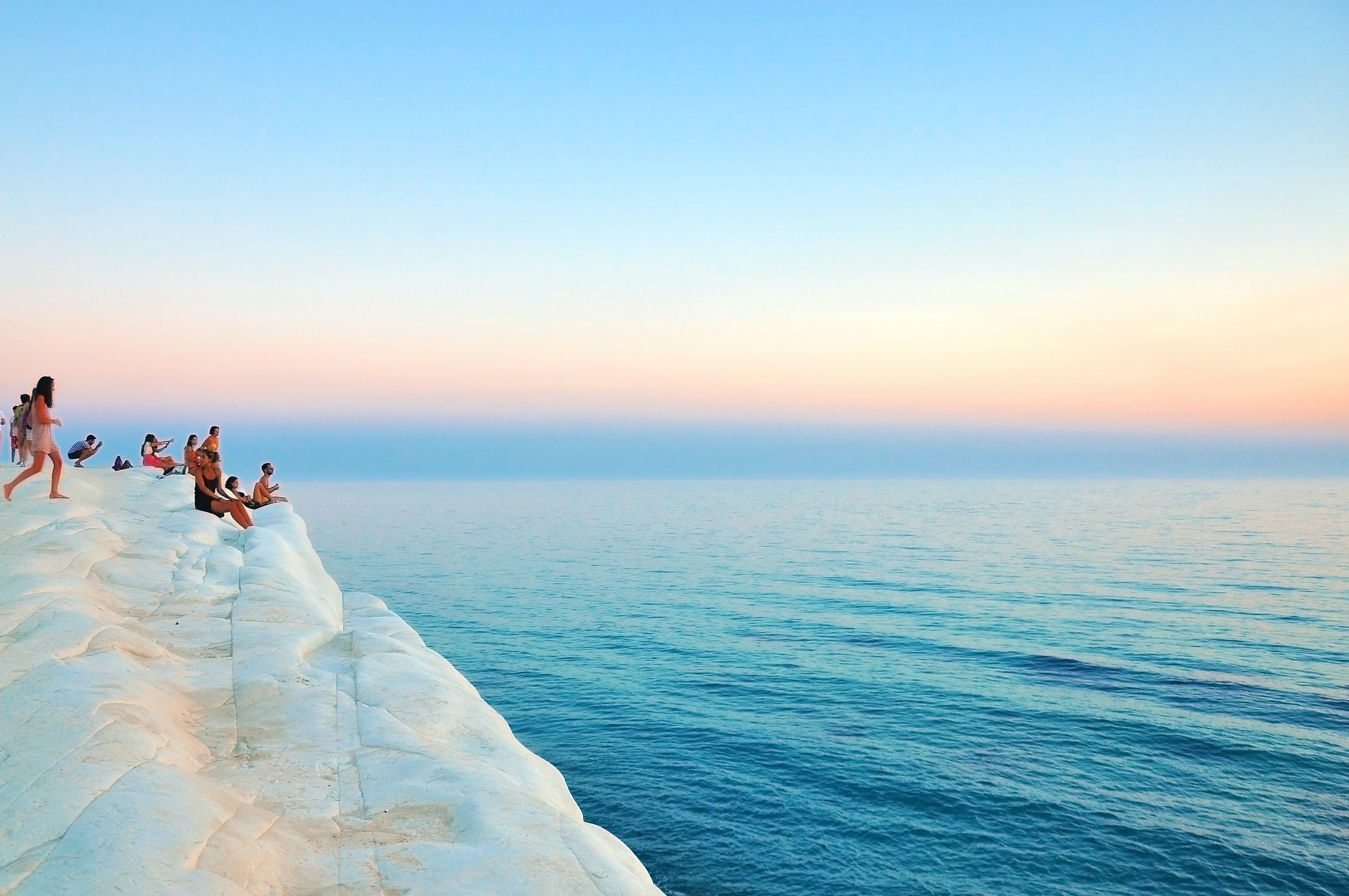 Summer view with people enjoying the ocean view from a white rock in Scala dei Turchi