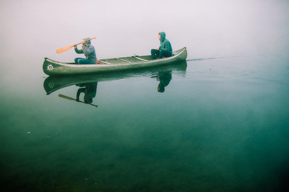 men riding on canoe