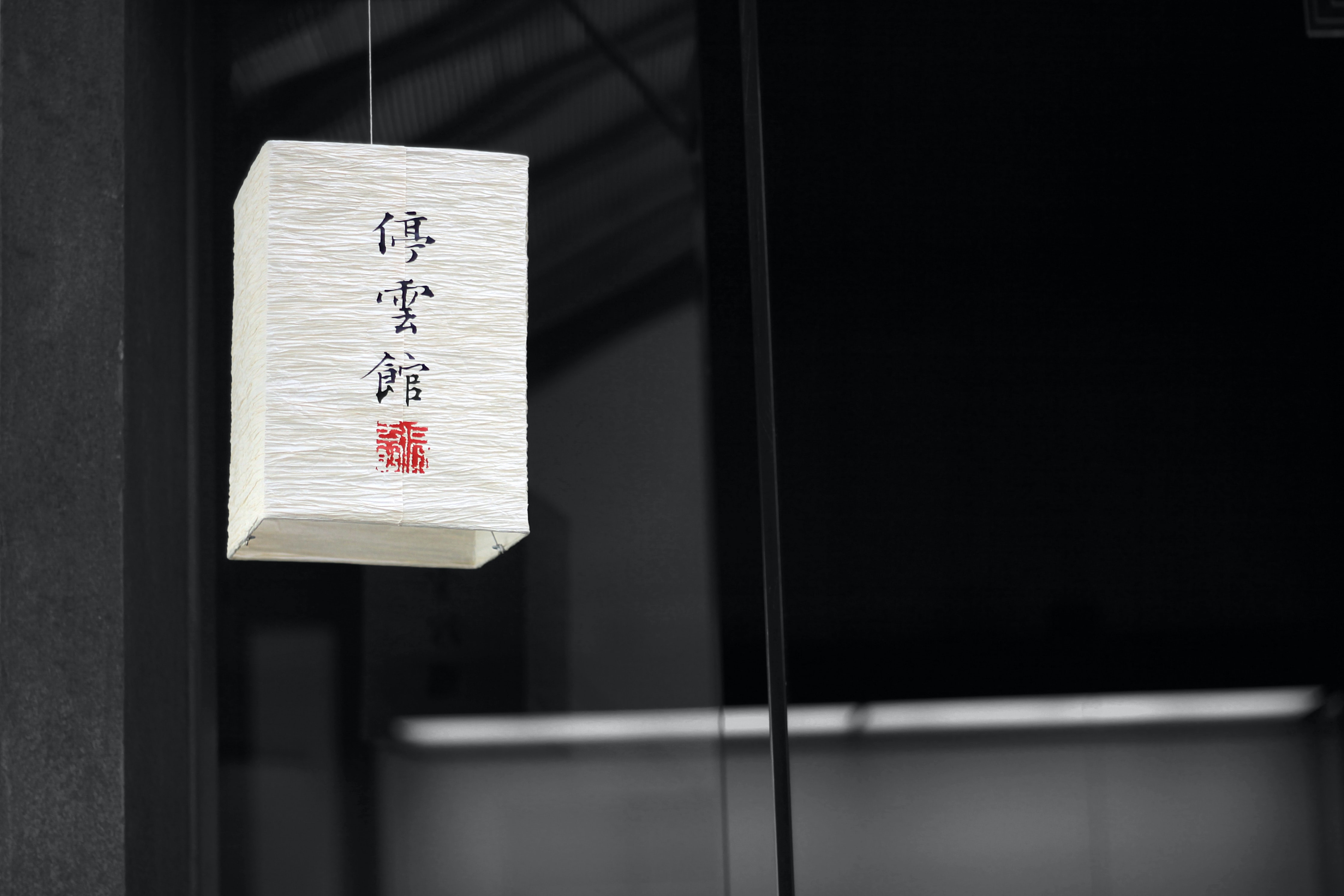 Chinese characters on a paper lantern hanging from a ceiling