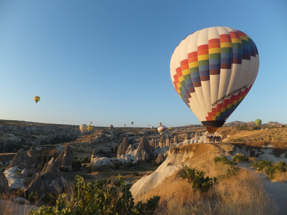 hot air balloons in flight above mountains