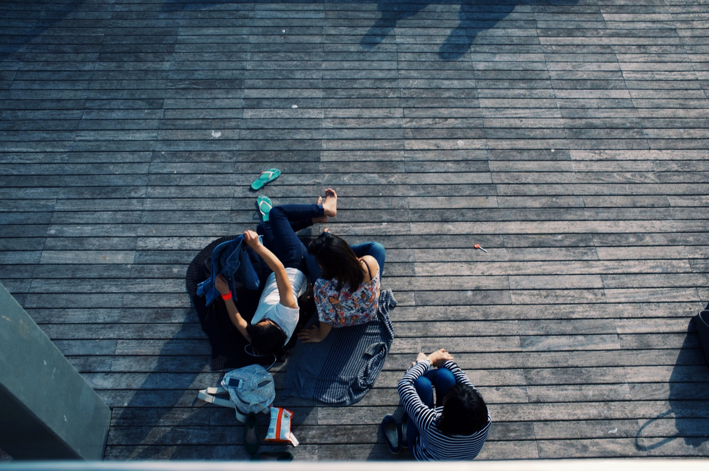 A group of people laying down on a deck, covering themselves with sweaters