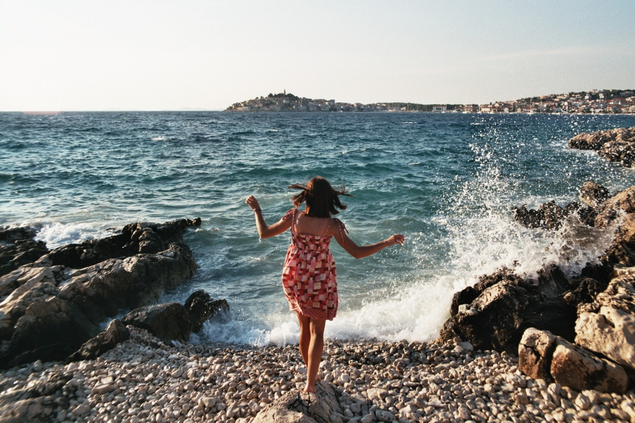 A woman in a dress standing on a rock on the coast with waves crashing against the nearby rocks