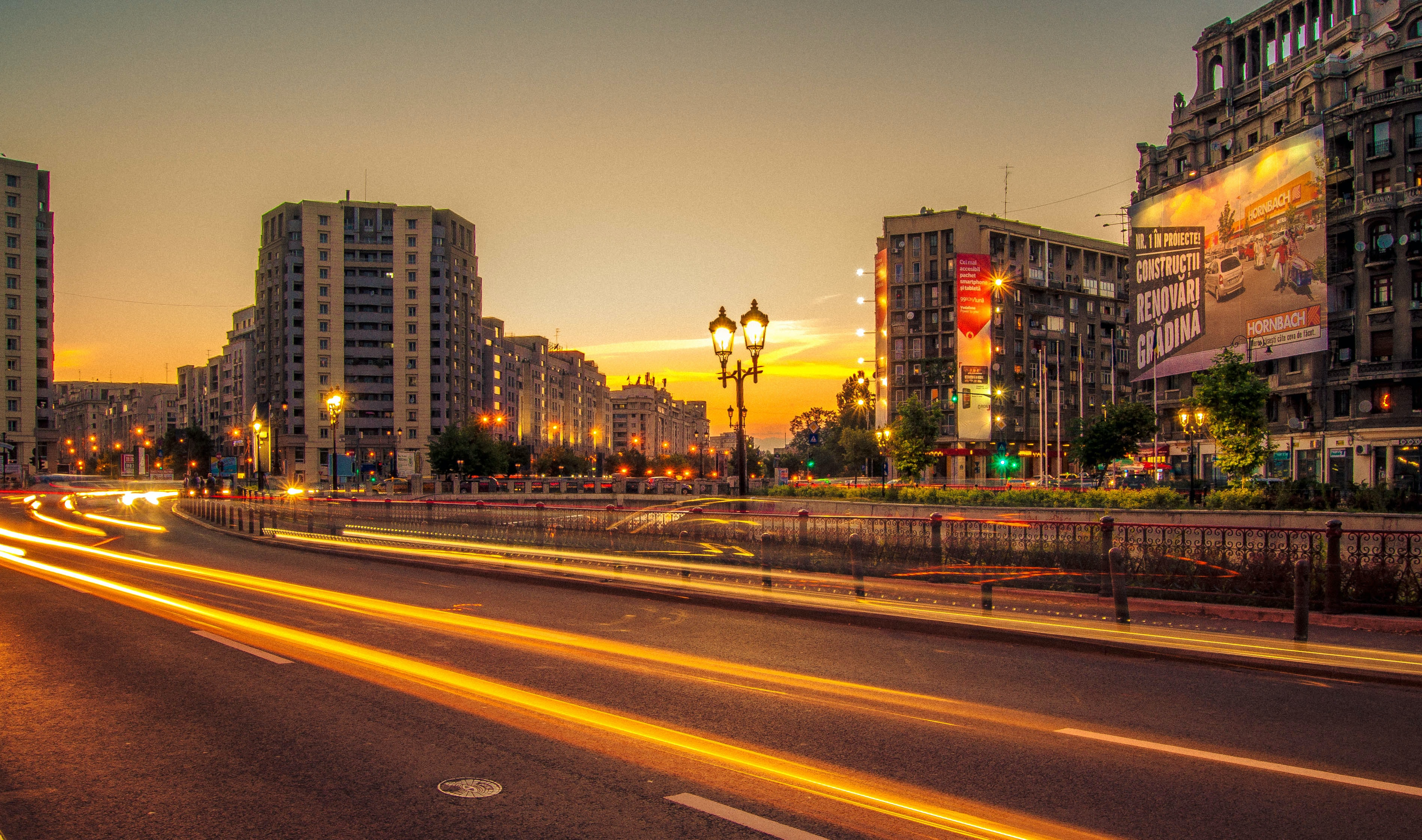 Orange light trails in the streets of a Romanian city during sunset