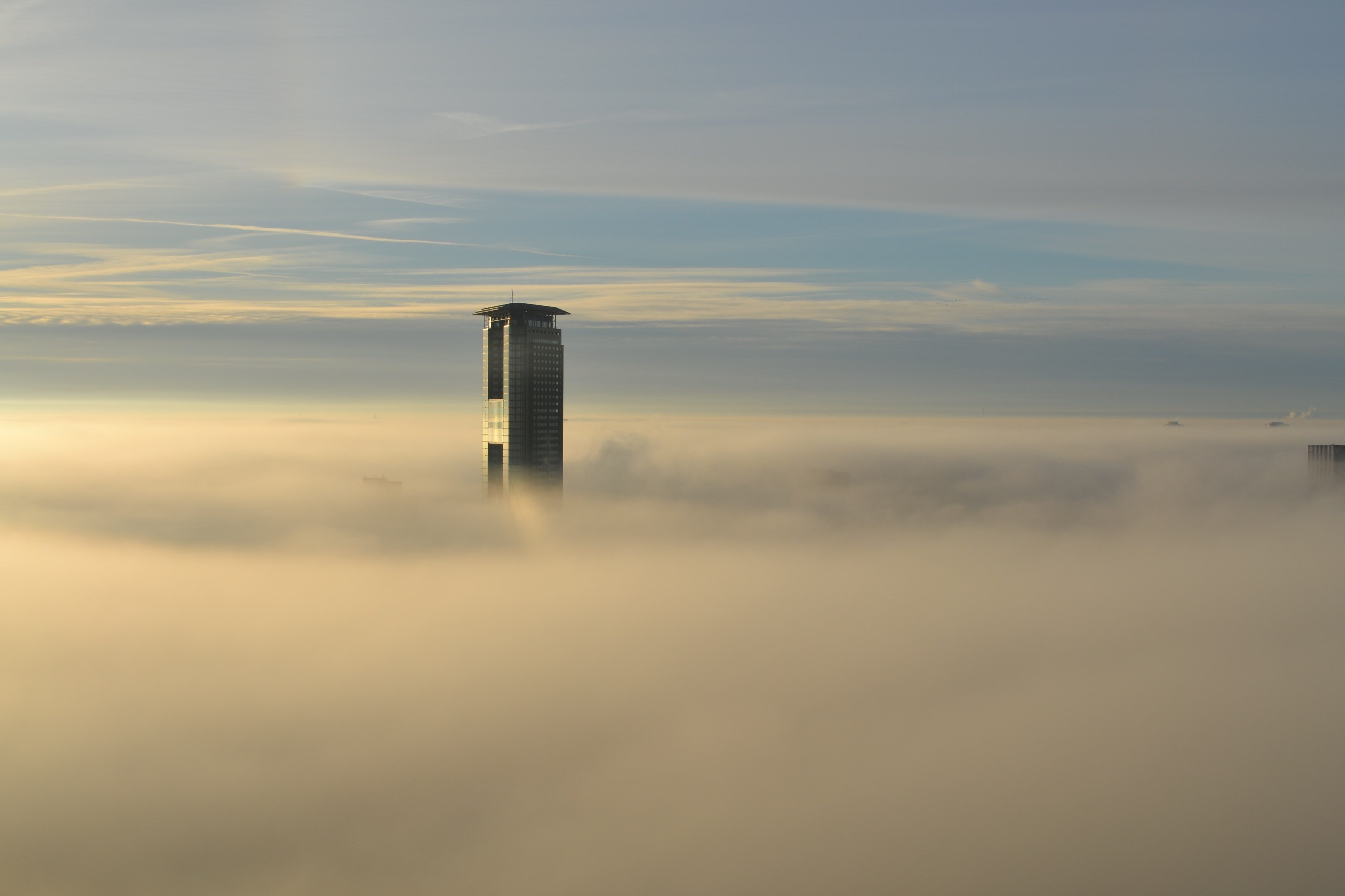 City skyscraper peeks through the clouds on a sunny day