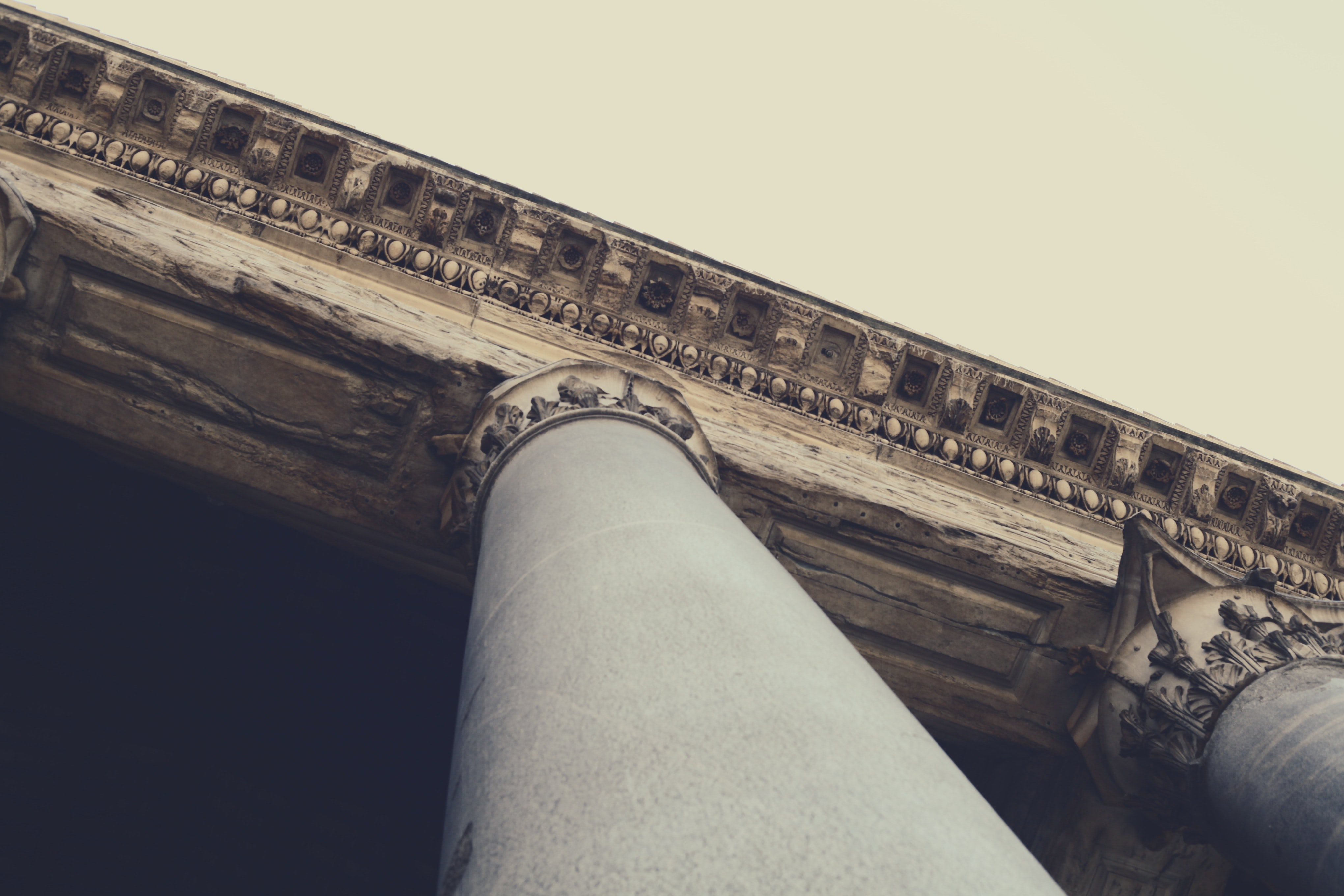 A shot looking up at a pillar with greek architectural features