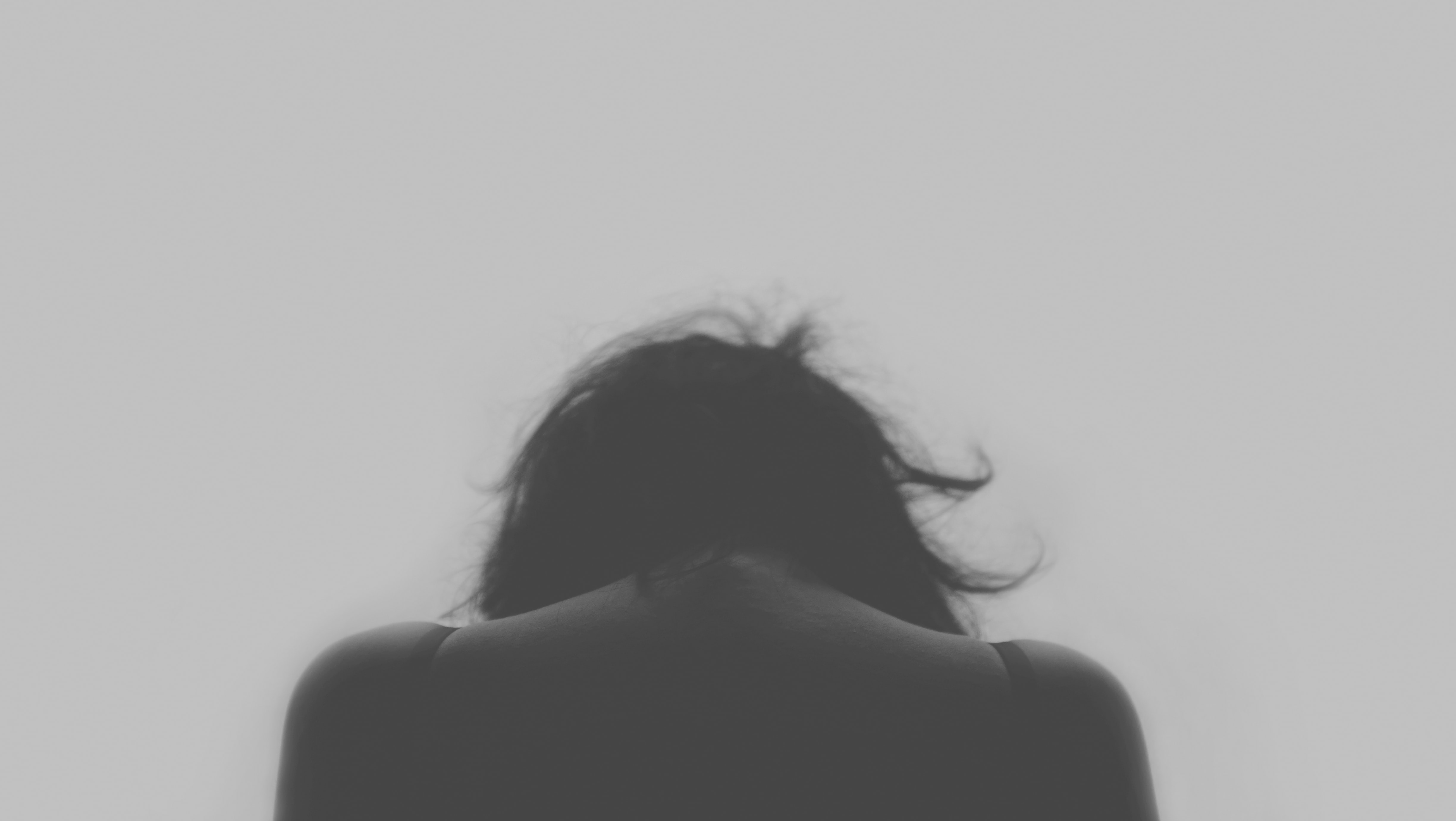 A black and white rear shot of the back of a woman's head and back, with her head bowed down in sadness