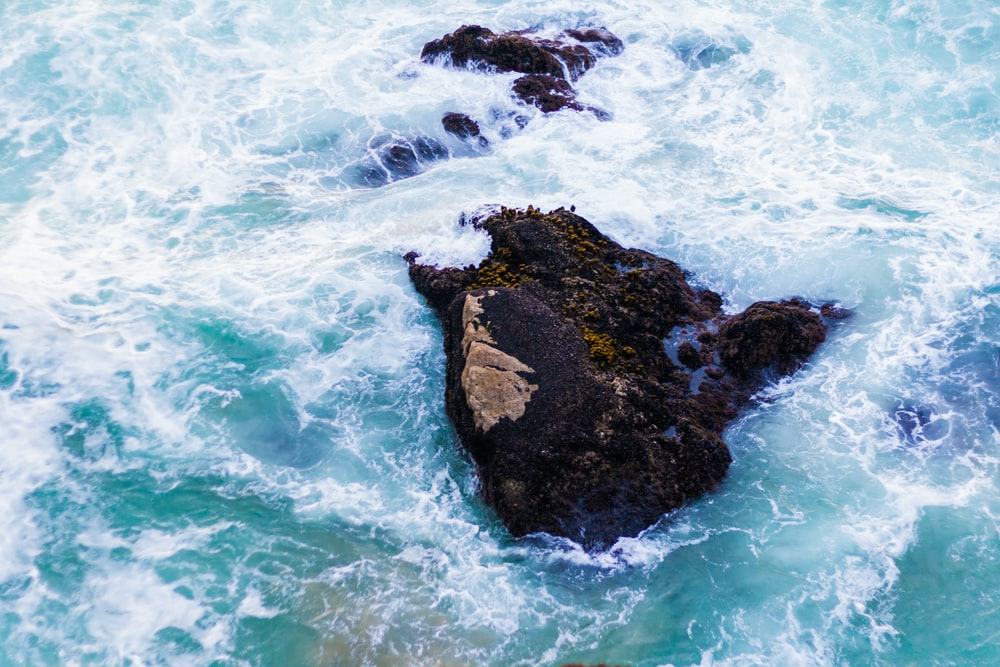 scenery of a rock on a body of water