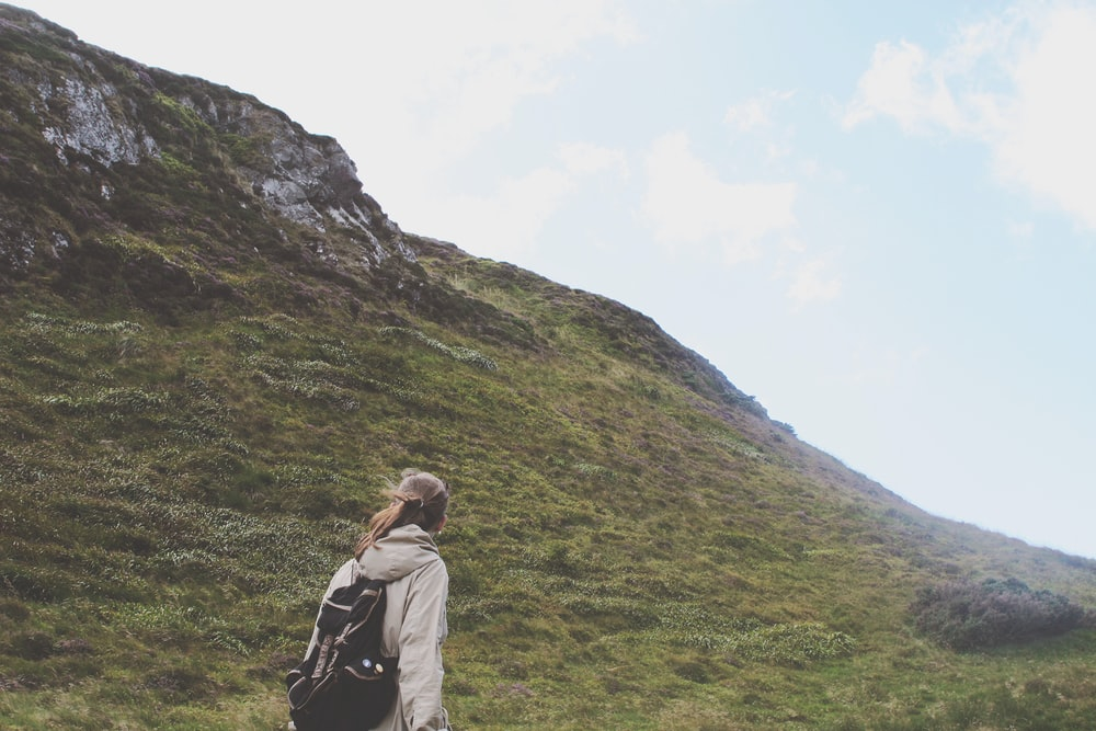 person walking on green mountain