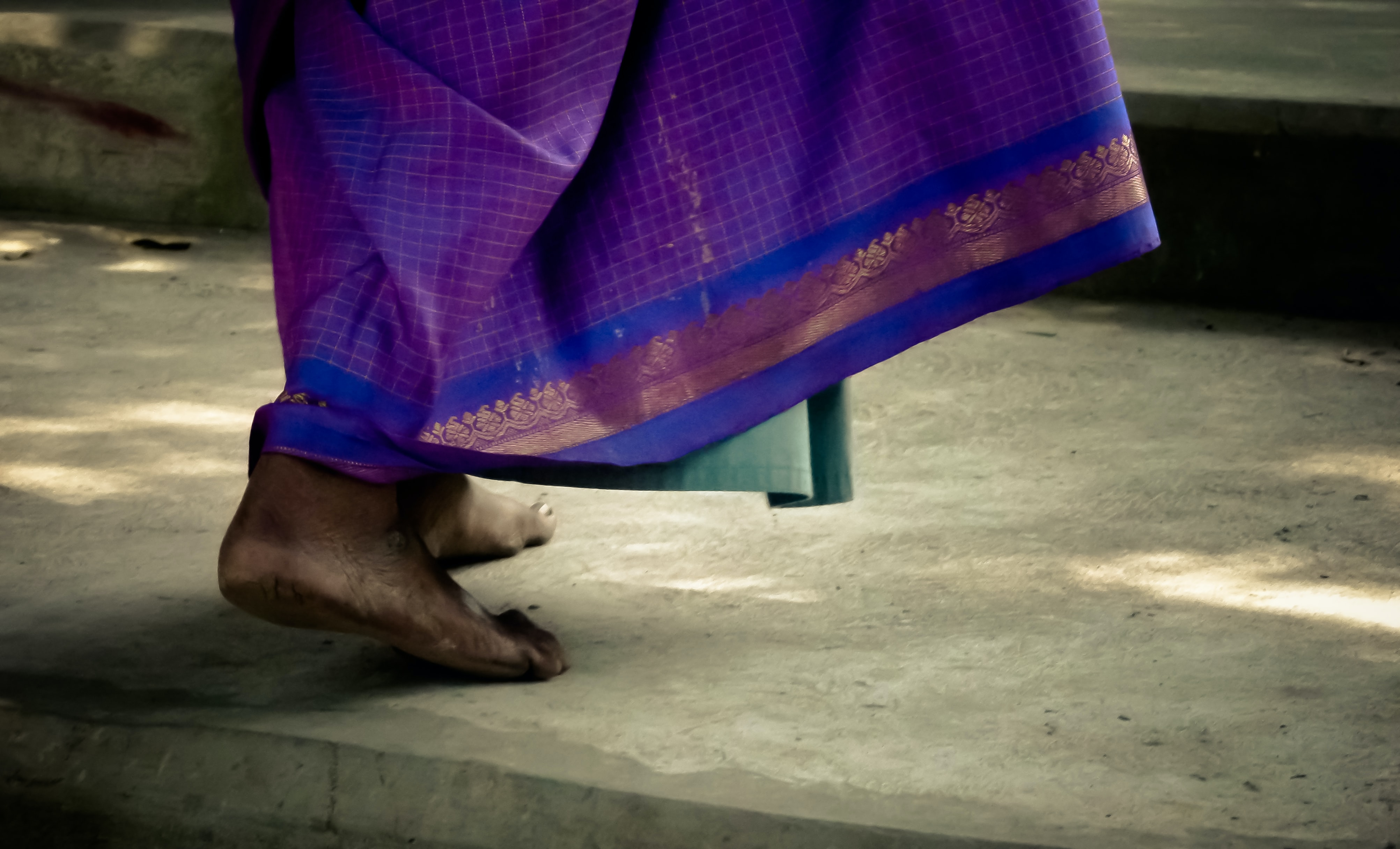 Woman's bare feet walk on the pavement as a saree brushes her ankles