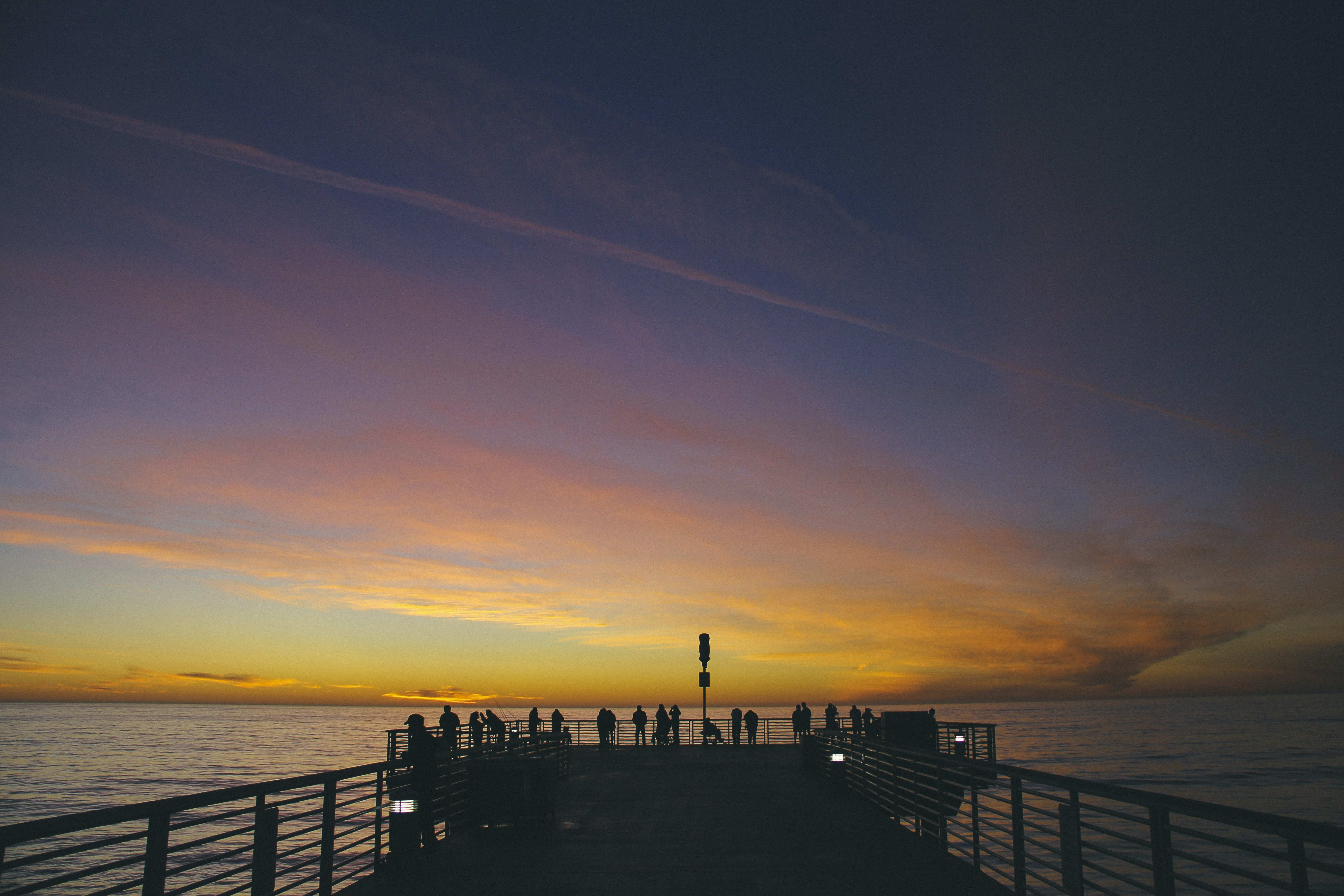 silhouette of people on dock near body of water during golden hour