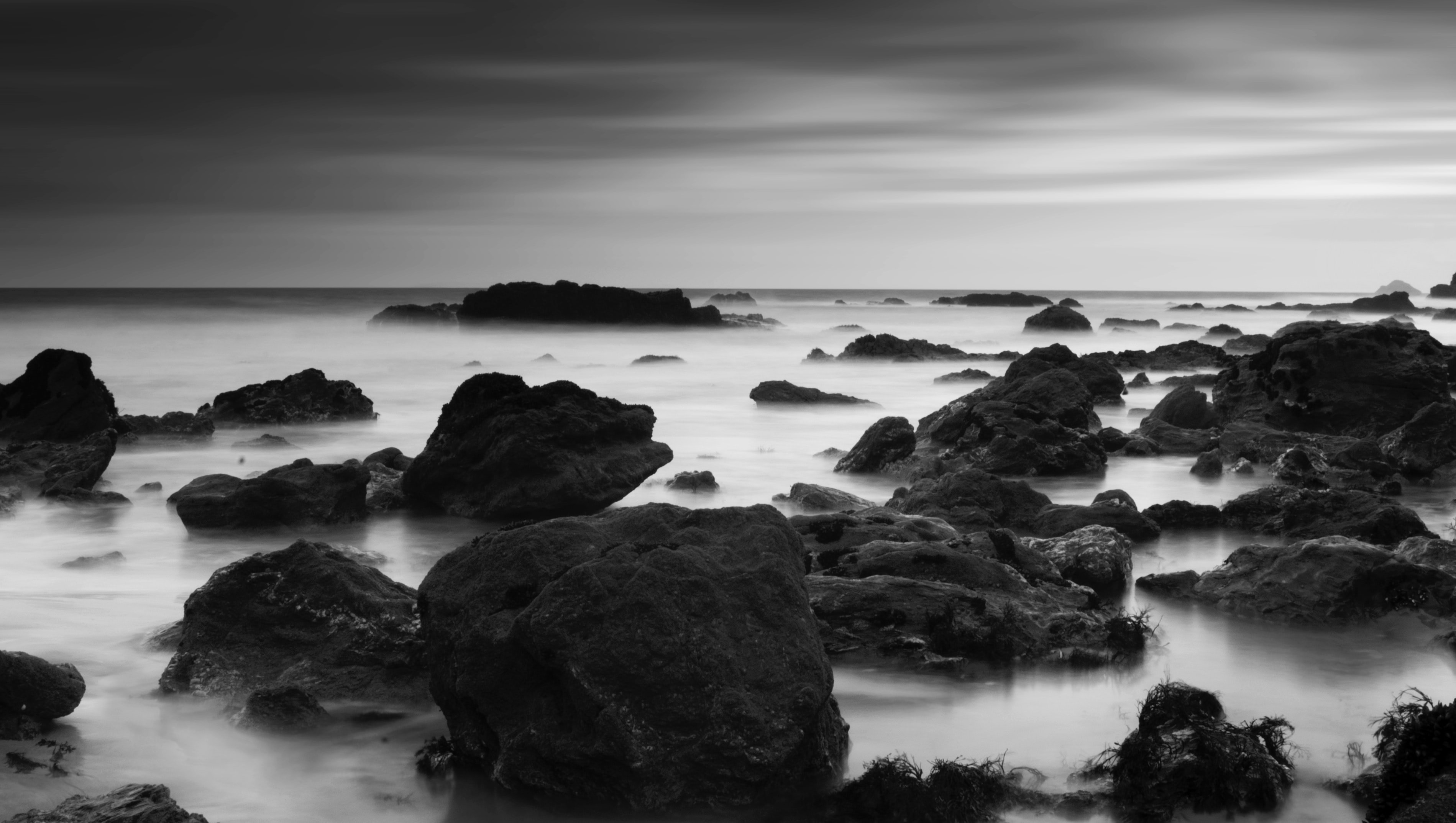 A black and white photo of rocks protruding from the ocean along the coast