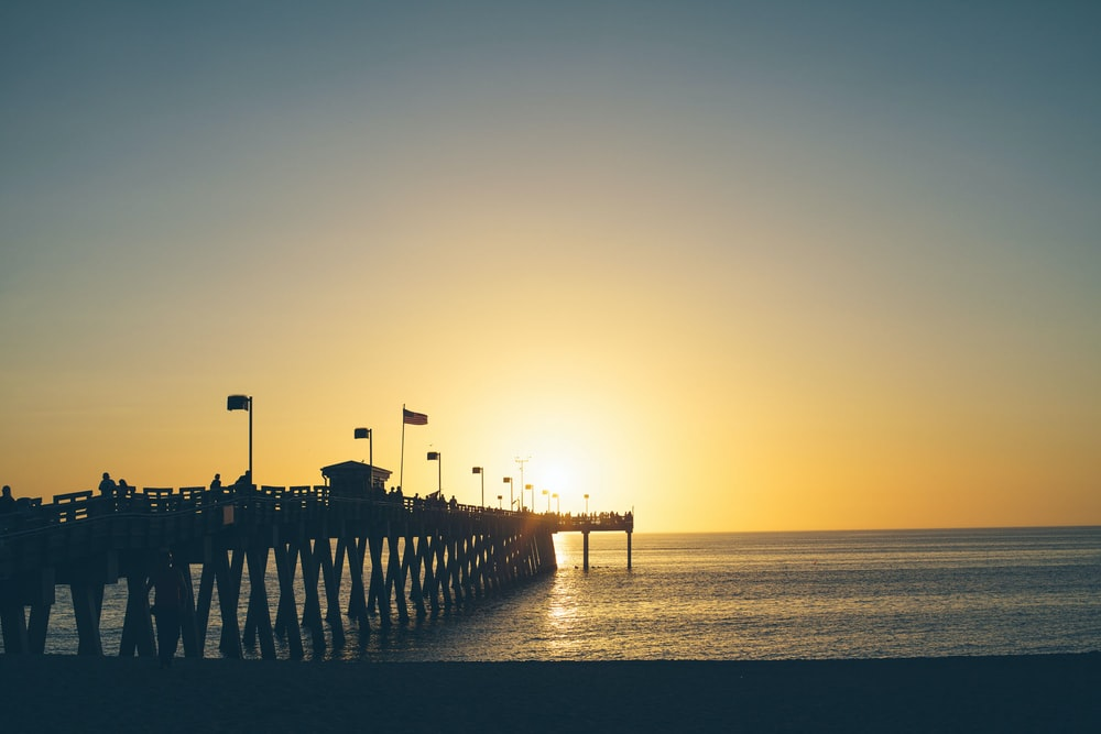 silhouette shot of dock and beach
