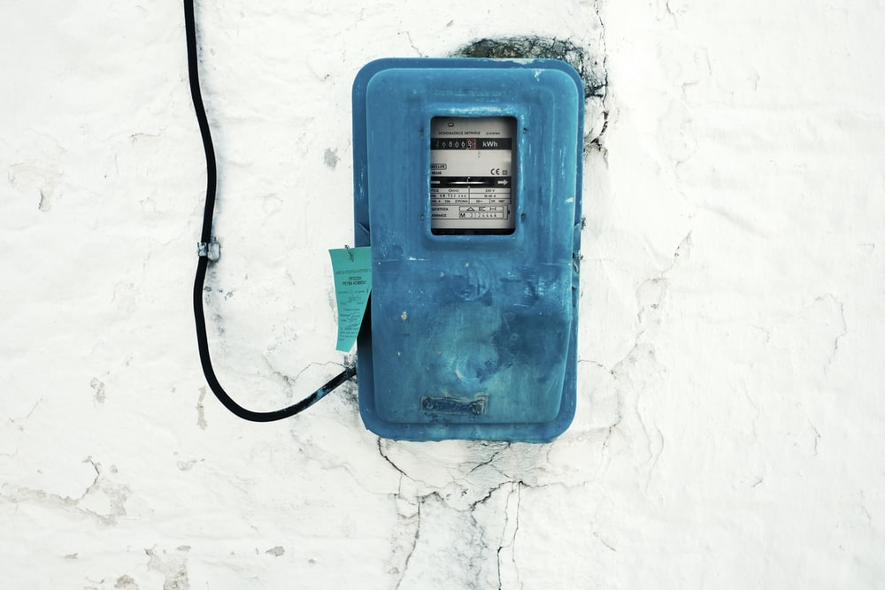 blue corded electronic appliance mounted on white painted wall
