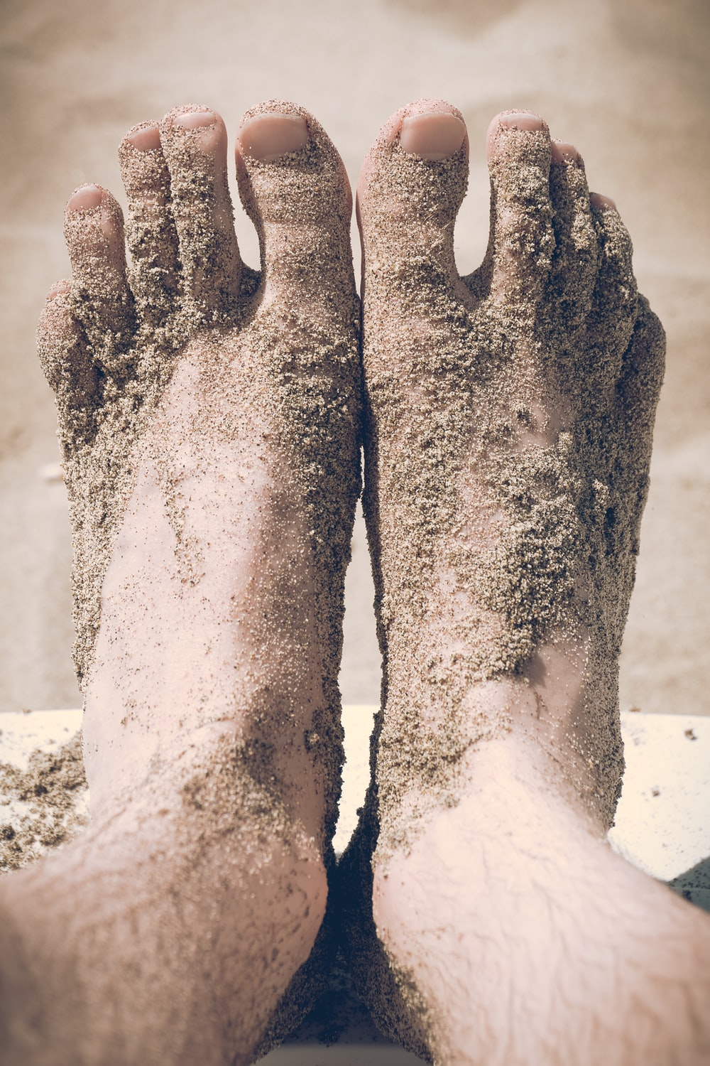 closeup photo of person's feet covered with sand