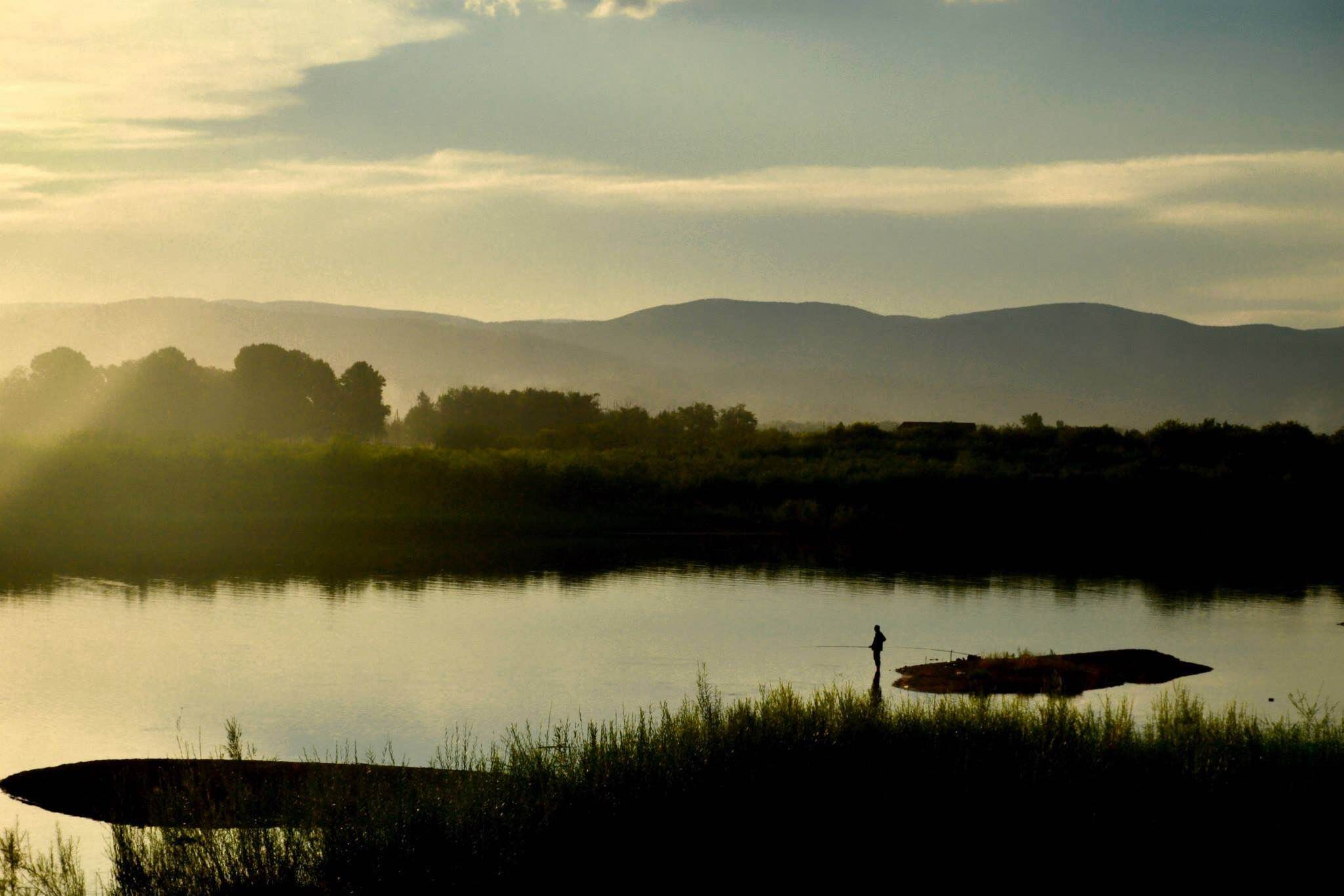 A tranquil shot of a lake with a silhouette of a lone fisherman in knee-high water