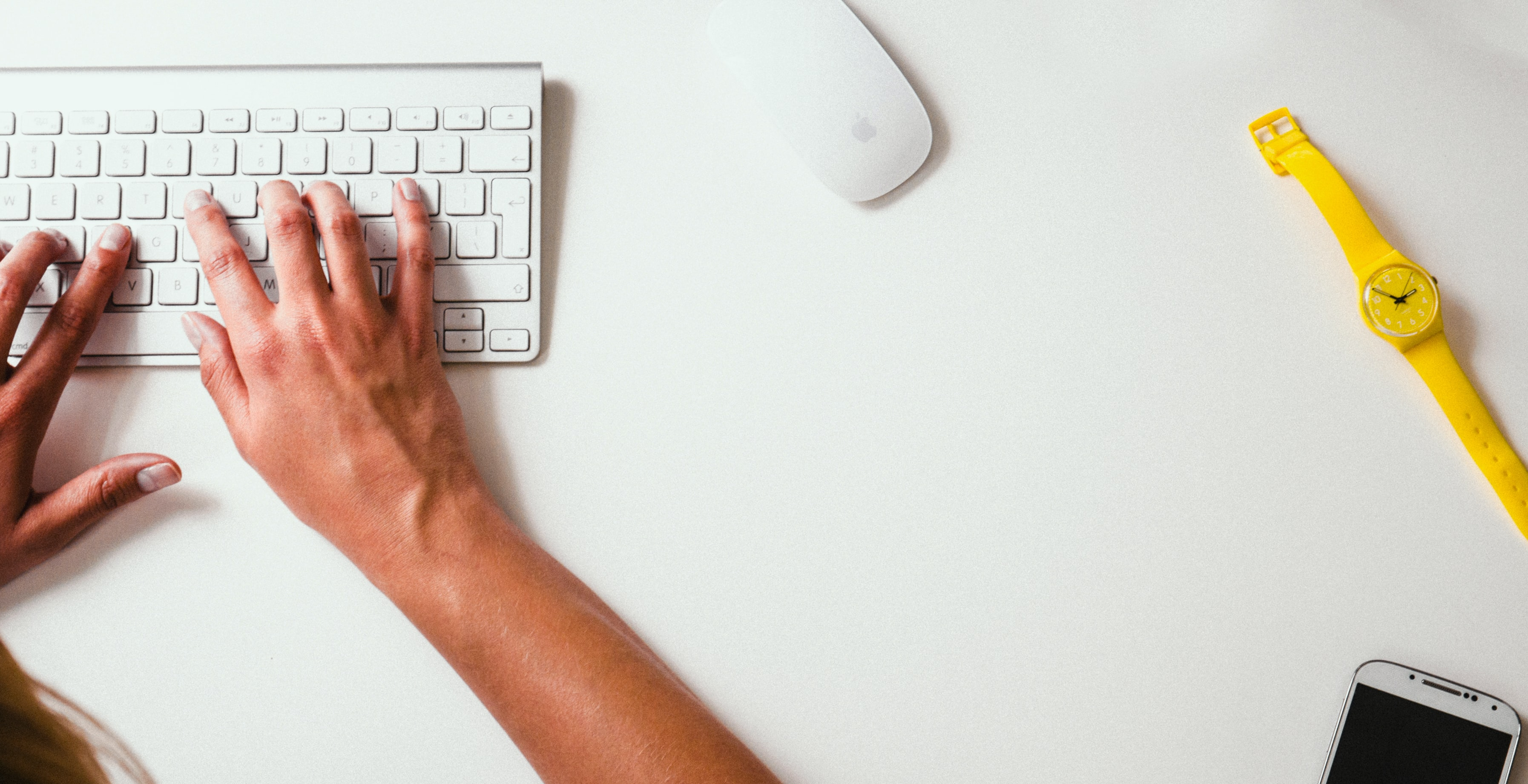The hands of a designer typing on the keyboard connected to a computer in an office setting.
