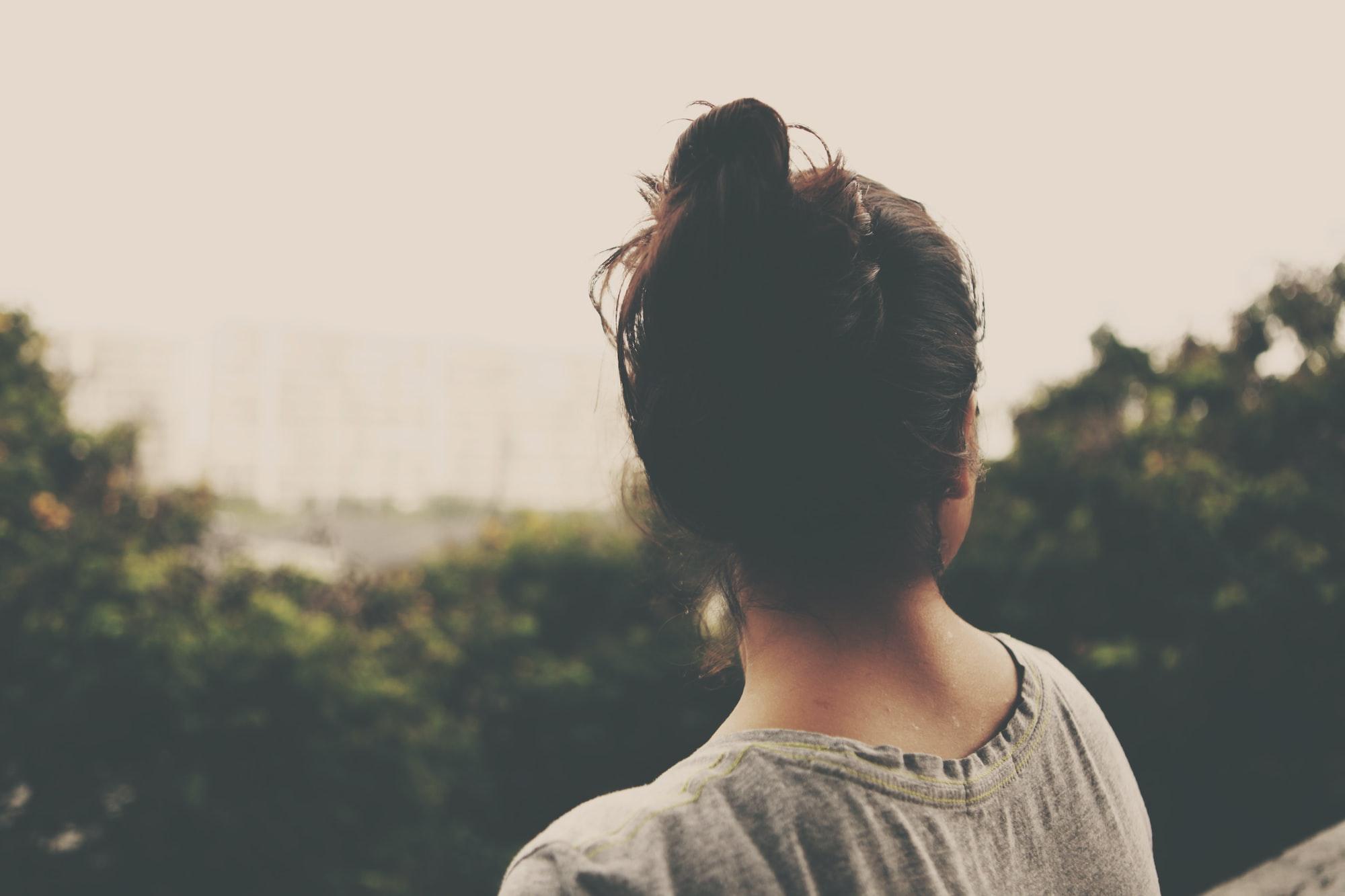 Back shot of a woman with dark hair in a bun, wearing a grey shirt.
