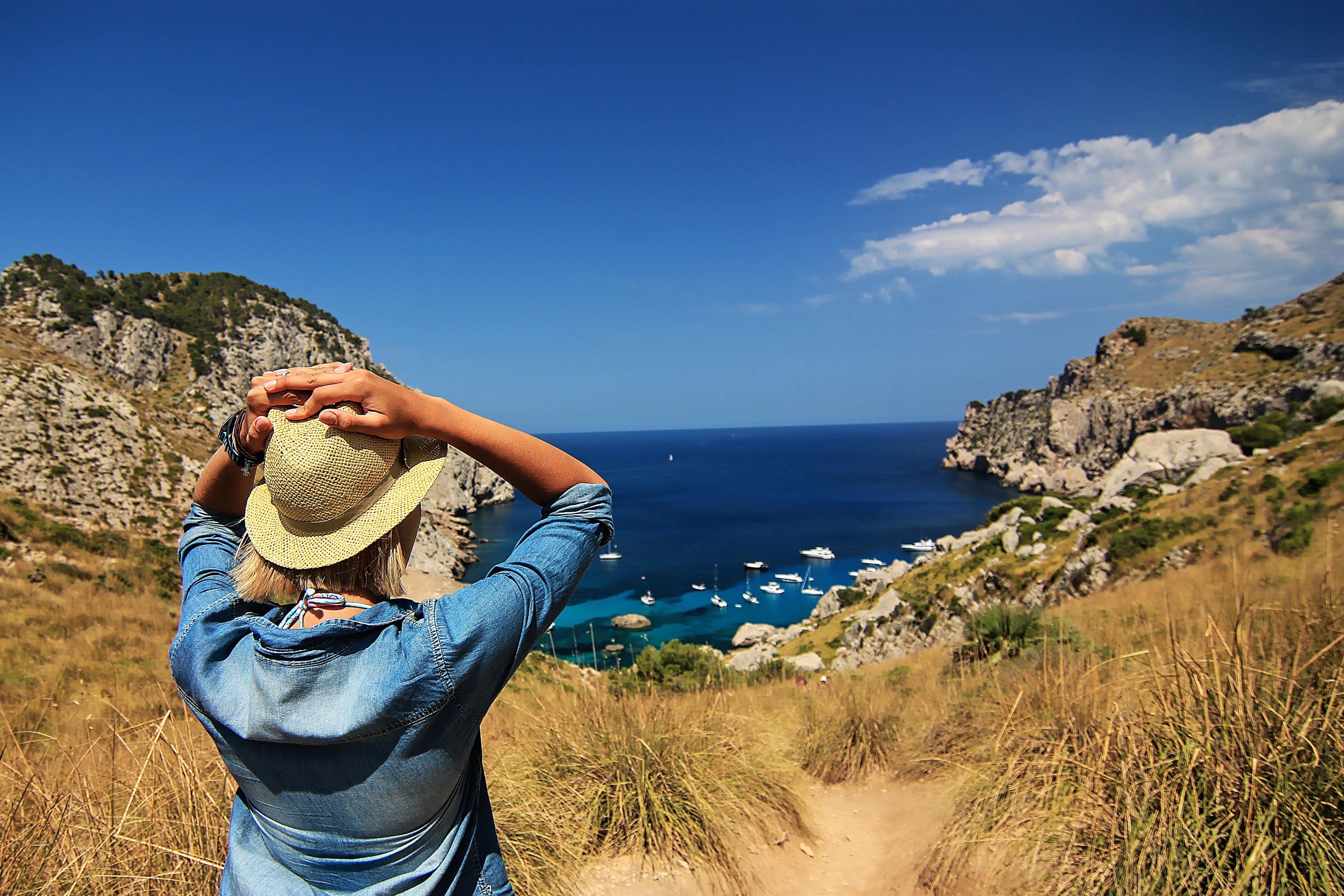 A woman in a hat and a denim jacket facing yachts in a deep blue bay encircled by cliffs