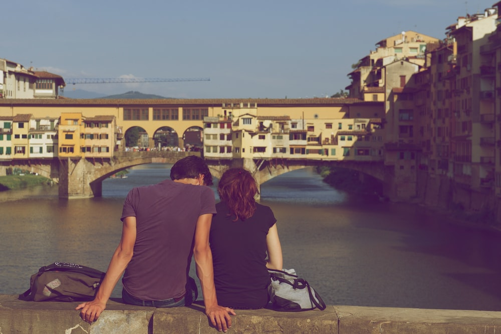 Couple sitting closely together on a ledge overlooking a river