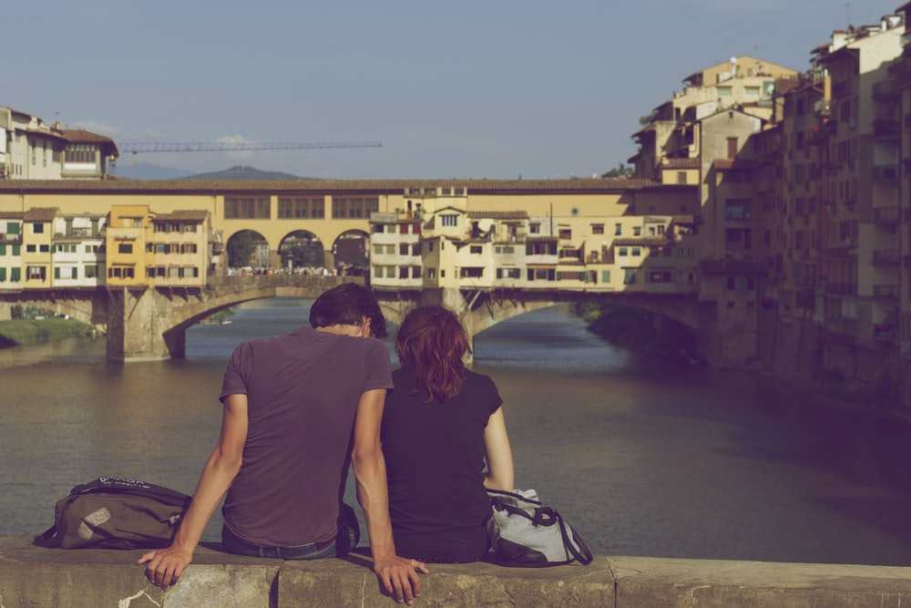 man and woman sitting together in front of body of water during daytime
