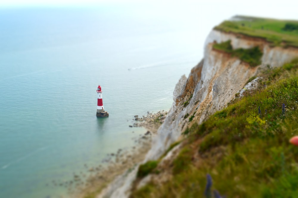 aerial photograph of red and white lighthouse on rock