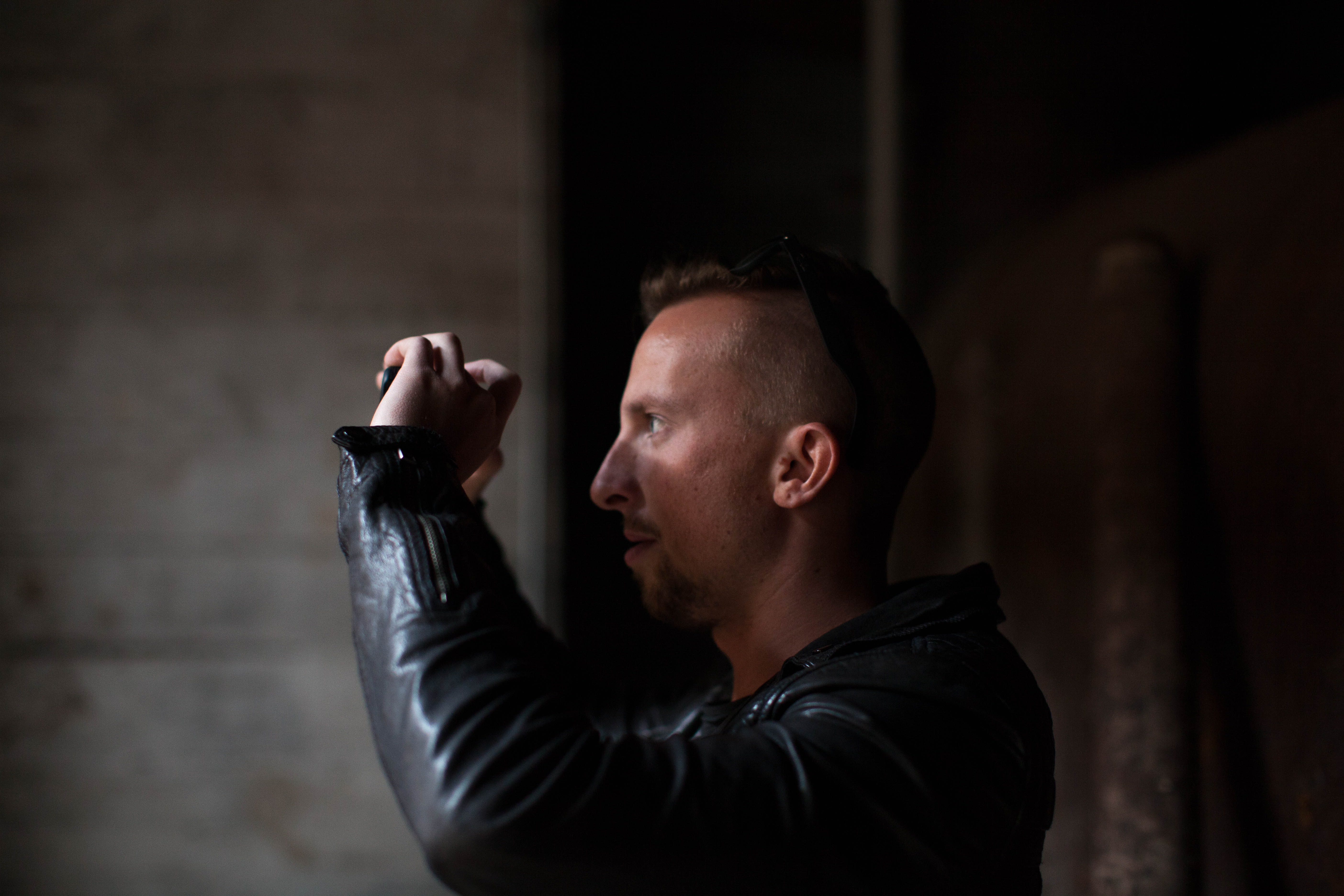 A man in a leather jacket in a dark area taking a picture on his phone