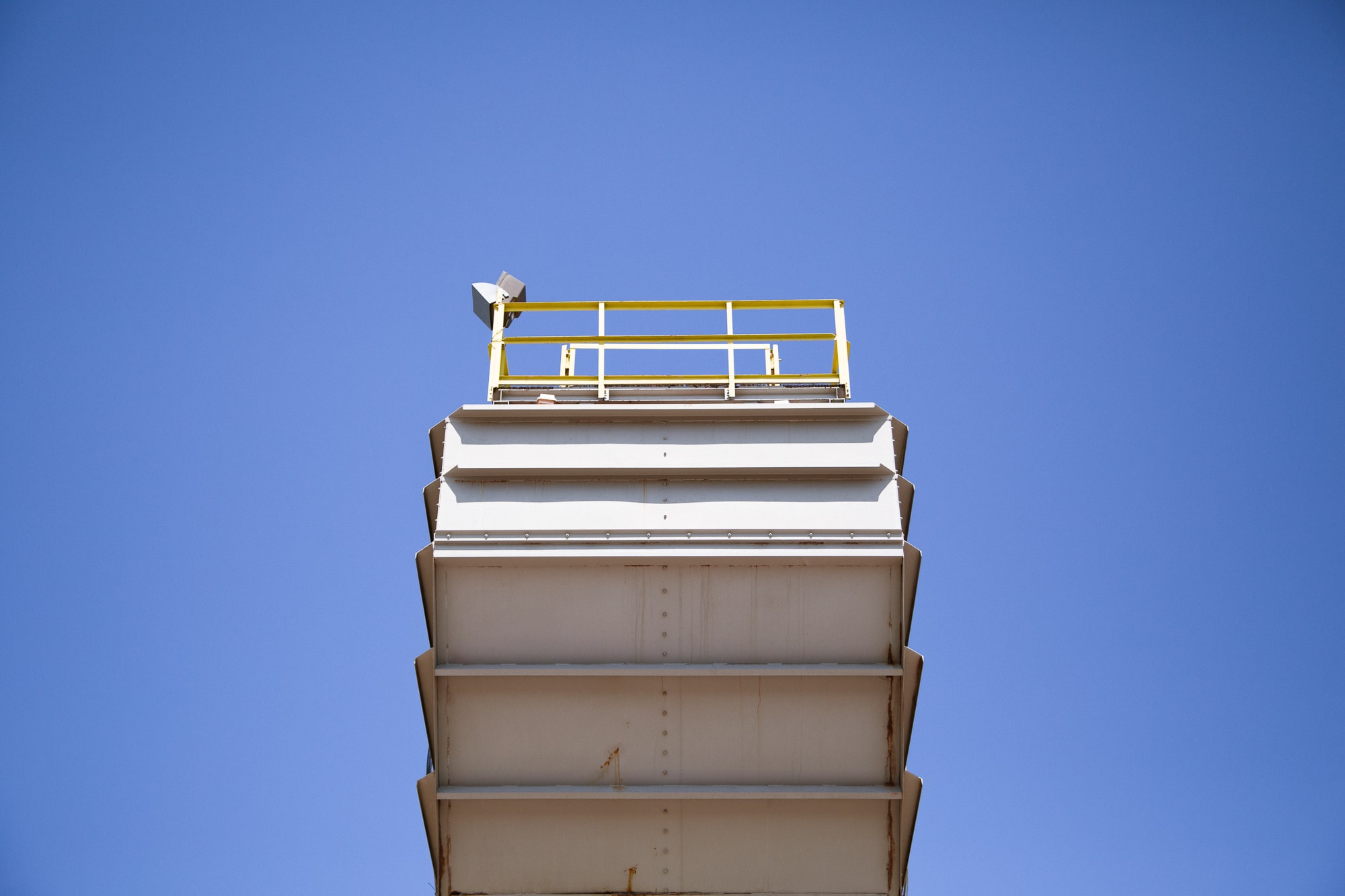 A low-angle shot of a high steel platform against a blue sky