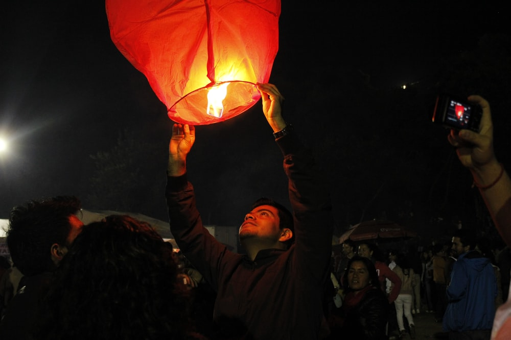 man holding lighted sky lantern