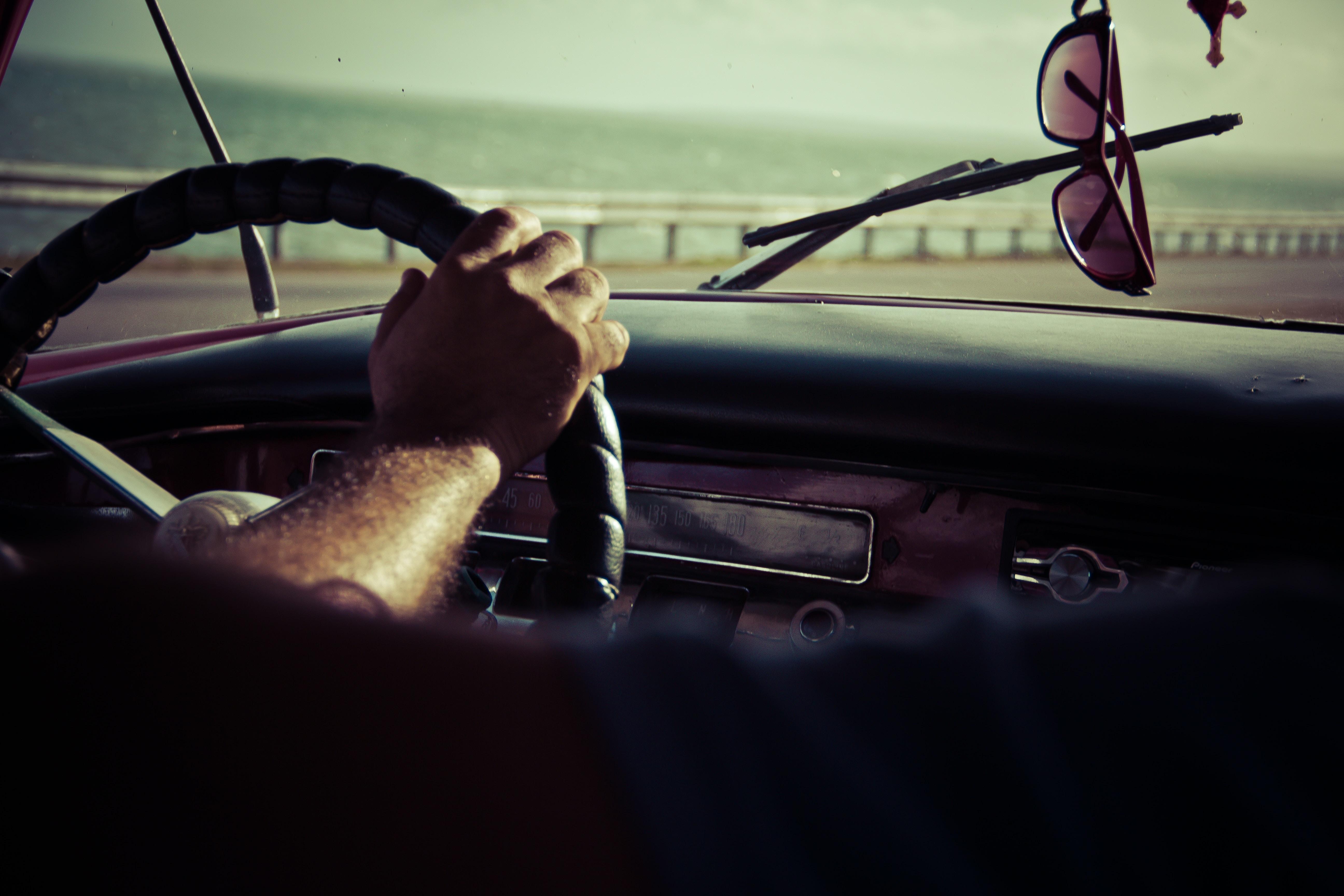 Interior back seat shot of man driving car on sunny day at coast