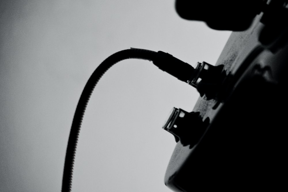 A black-and-white shot of a wire plugged in into a guitar